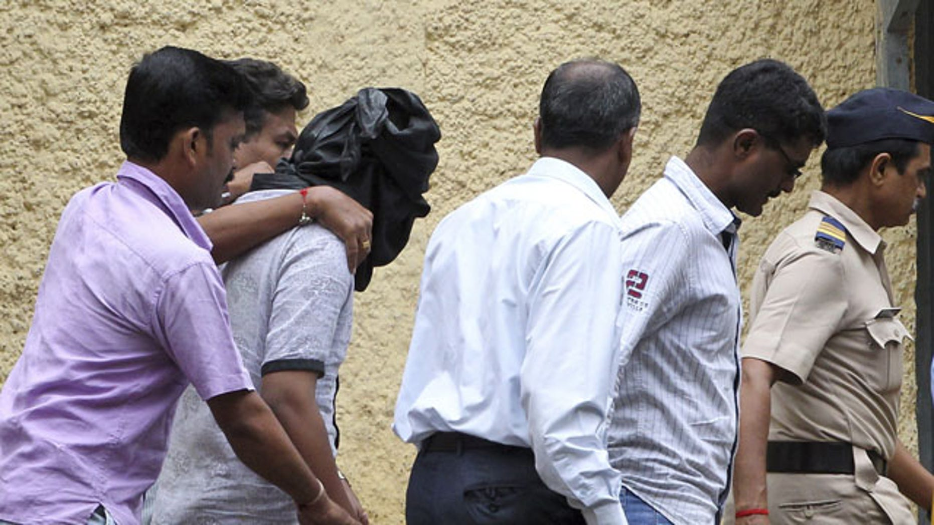 August 24, 2013: Police officials escort an accused, head covered with black cloth, in the gang rape of a young photojournalist in the Indian financial hub of Mumbai, India.