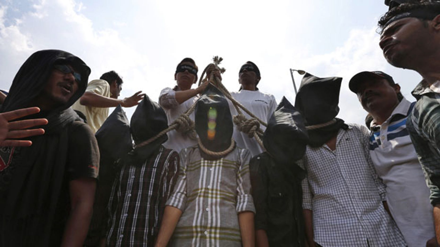 September 10, 2013: Indian protesters stage a mock hanging scene to demand death sentence for four men after a judge convicted them in the fatal gang rape of a young woman on a moving New Delhi bus last year, in New Delhi, India.