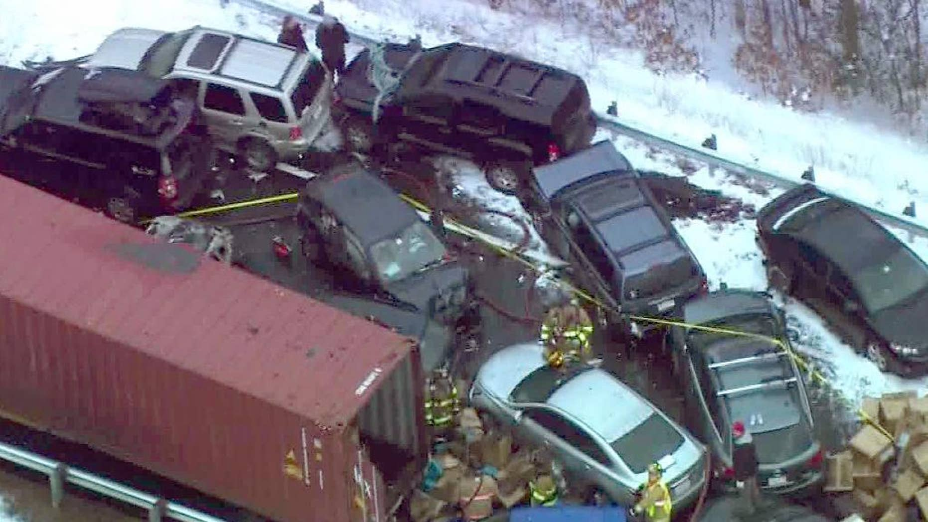 In this frame grab made from aerial video provided by WCVB-TV, emergency personnel work the scene along Interstate Route 93 near Ashland, N.H., where a New Hampshire State Police spokesman says 35 vehicles were involved in two separate pileups after some fast-moving snow squalls, Friday, Jan. 2, 2015. (AP Photo/WCVB-TV)