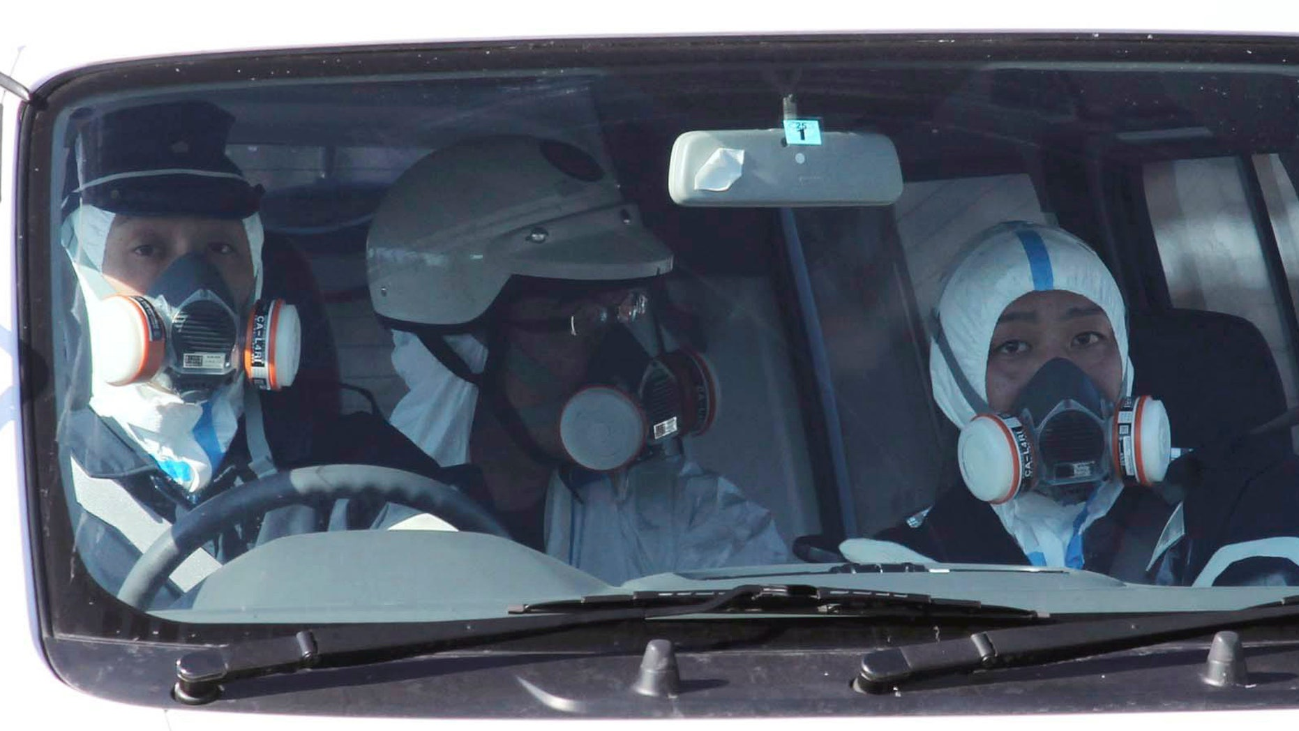 March 12: Police officers wearing gas masks patrol in the area of the Fukushima power plant's Unit 1 in Okumamachi, Fukushima Prefecture, northern Japan, amid fears that a part of the plant could meltdown after being hit by a powerful earthquake and tsunami Friday. (AP/The Yomiuri Shimbun)