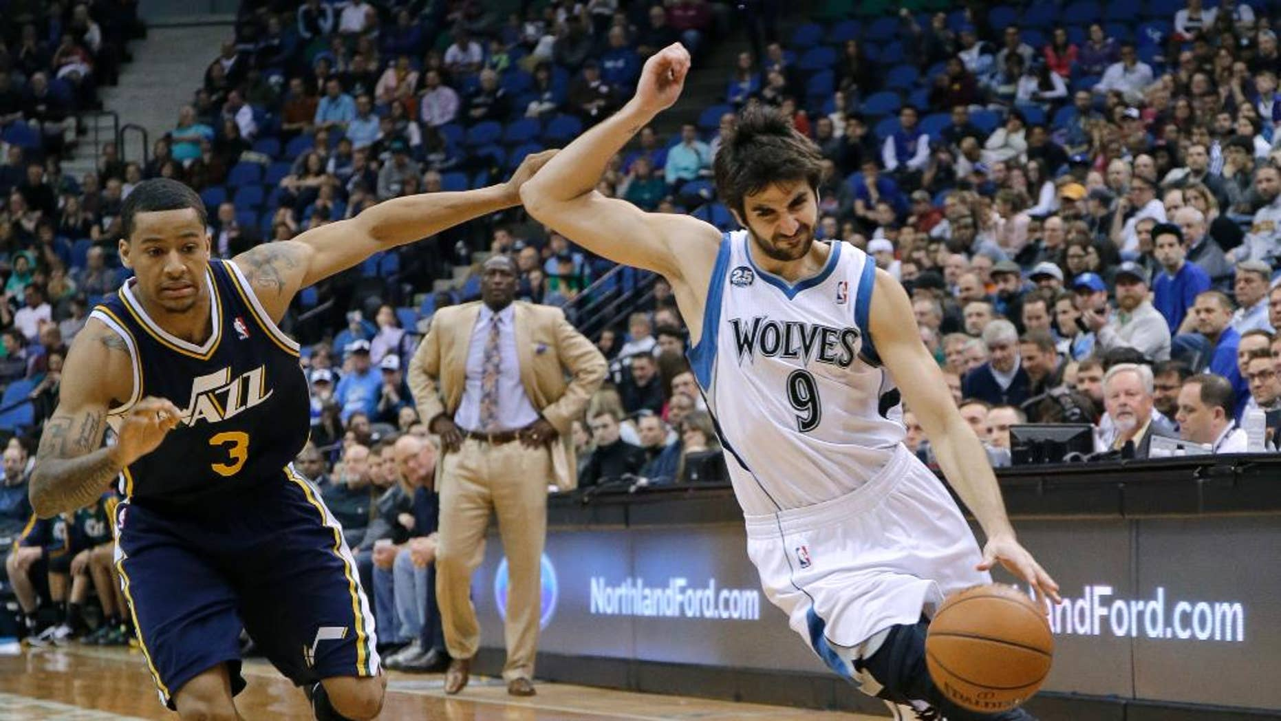 Minnesota Timberwolves guard Ricky Rubio (9), of Spain, tries to shake off Utah Jazz guard Trey Burke (3) on a drive during the fourth quarter of an NBA basketball game in Minneapolis, Wednesday, April 16, 2014. The Jazz won 136-130 in double overtime. (AP Photo/Ann Heisenfelt)