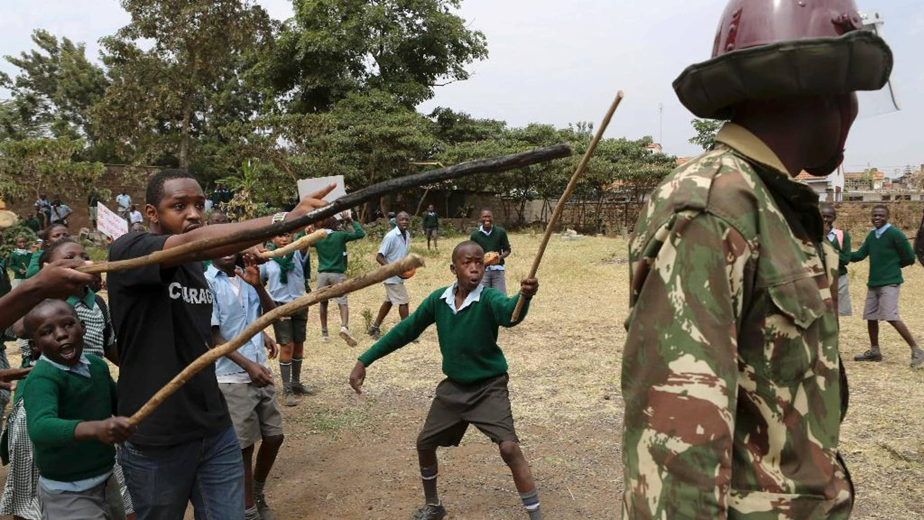 Kenyan school pupils and activists challenge riot police during a protest against the removal of their school's playground, at the Langata Road Primary School, in Nairobi, Kenya Monday, Jan. 19, 2015. Kenyan police tear-gassed schoolchildren demonstrating against the removal of their school's playground, the land of which has been allegedly grabbed by a powerful politician, according to a Kenyan human rights activist. (AP Photo/Brian Inganga)