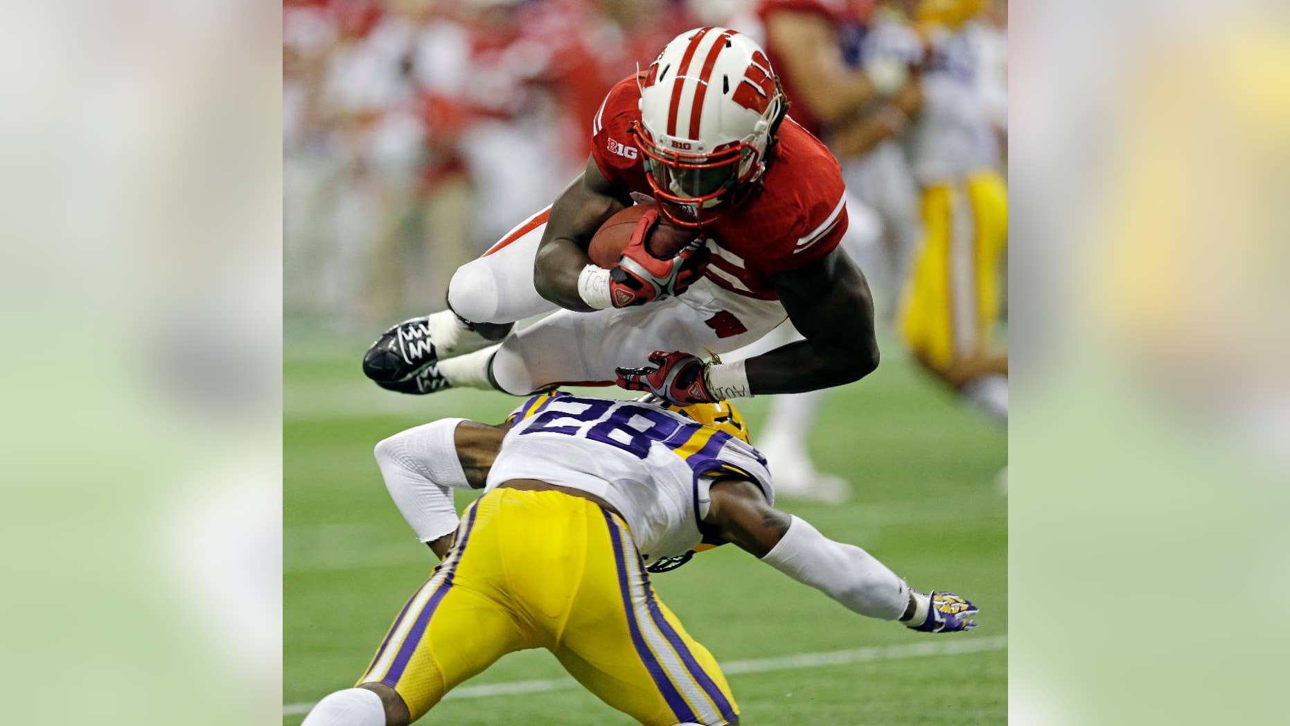 Wisconsin's Melvin Gordon leaps over LSU safety Jalen Mills (28) for a 14-yard touchdown run during the first half of an NCAA college football game Saturday, Aug. 30, 2014, in Houston. (AP Photo/David J. Phillip)