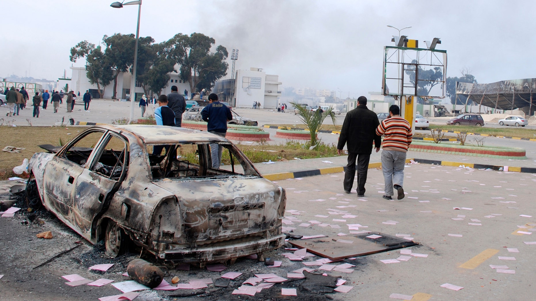 Feb. 21: Residents are seen walking past a burned-out vehicle in Benghazi, Libya. Stocks have dropped and oil prices are on the rise as protests sweep through the Libya.