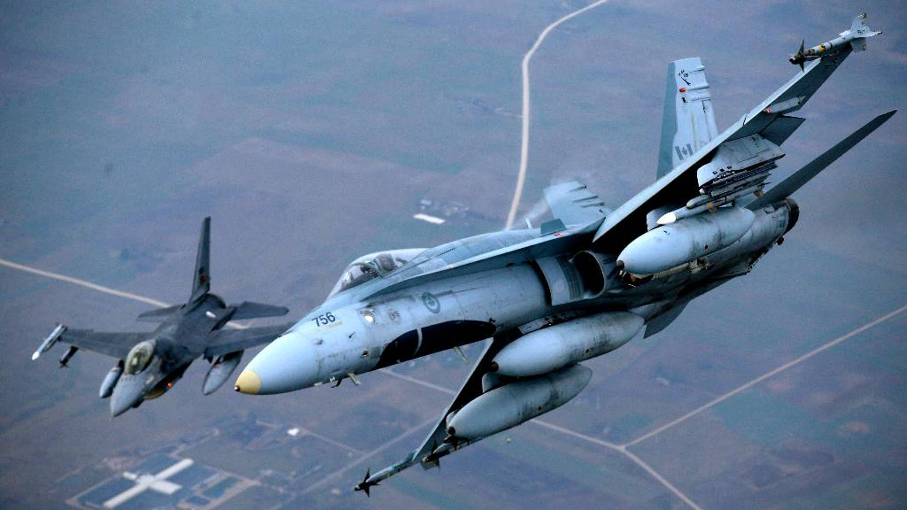 "A Portuguese military fighter jet, left, and a Canadian military fighter jet participating in NATO's Baltic Air Policing Mission operate in Lithuanian airspace, Thursday, Nov. 20, 2014. NATO, which has 16 fighter jets in the region monitoring Baltic airspace, said it regularly launches jets to identify ""unknown or potentially hostile aircraft"" in the proximity of national airspace. (AP Photo/Mindaugas Kulbis)"