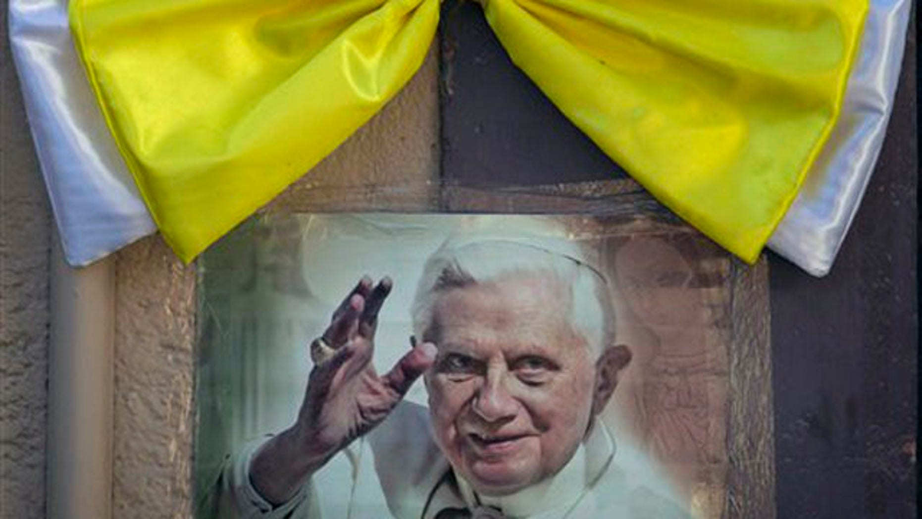 March 22, 2012: An image of Pope Benedict XVI is taped to a wall, topped with a Vatican-colored bow, in Leon, Mexico.