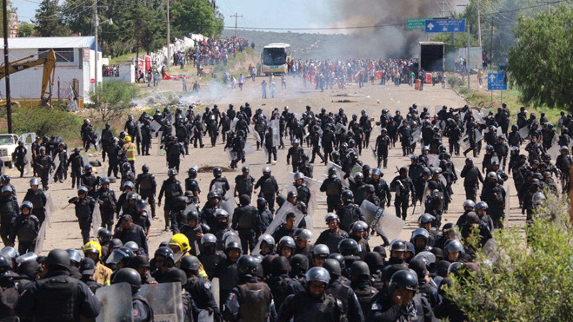 Riot police are forced to fall back as they battle with protesting teachers who were blocking a federal highway in the state of Oaxaca, near the town of Nochixtlan, Mexico, Sunday, June 19, 2016. The teachers are protesting against plans to overhaul the country's education system which include federally mandated teacher evaluations. (AP Photo/Luis Alberto Cruz Hernandez)