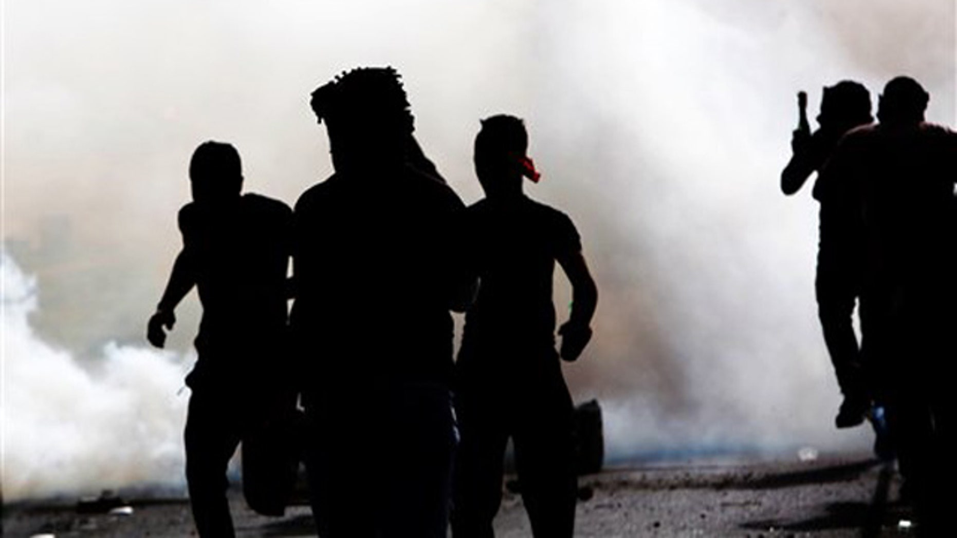 March 31, 2012: Bahraini anti-government protesters react to tear gas fired by riot police Saturday.