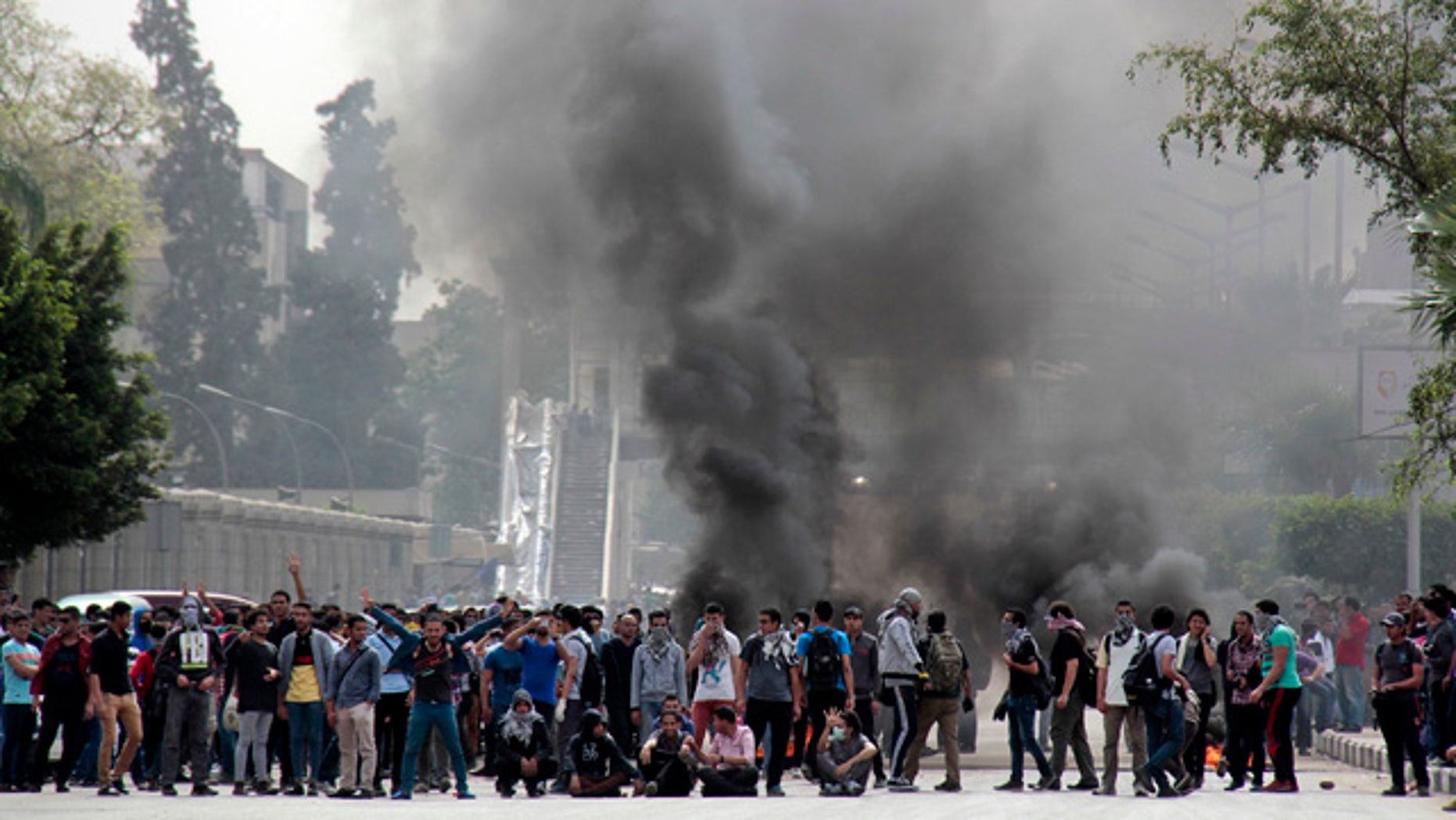 April 23, 2014: Pro-Muslim Brotherhood students block a road with burning tires and chant slogans against the police and army outside the main campus of Cairo University, in Cairo, Egypt. (AP Photo/Aly Hazzaa, El Shorouk)