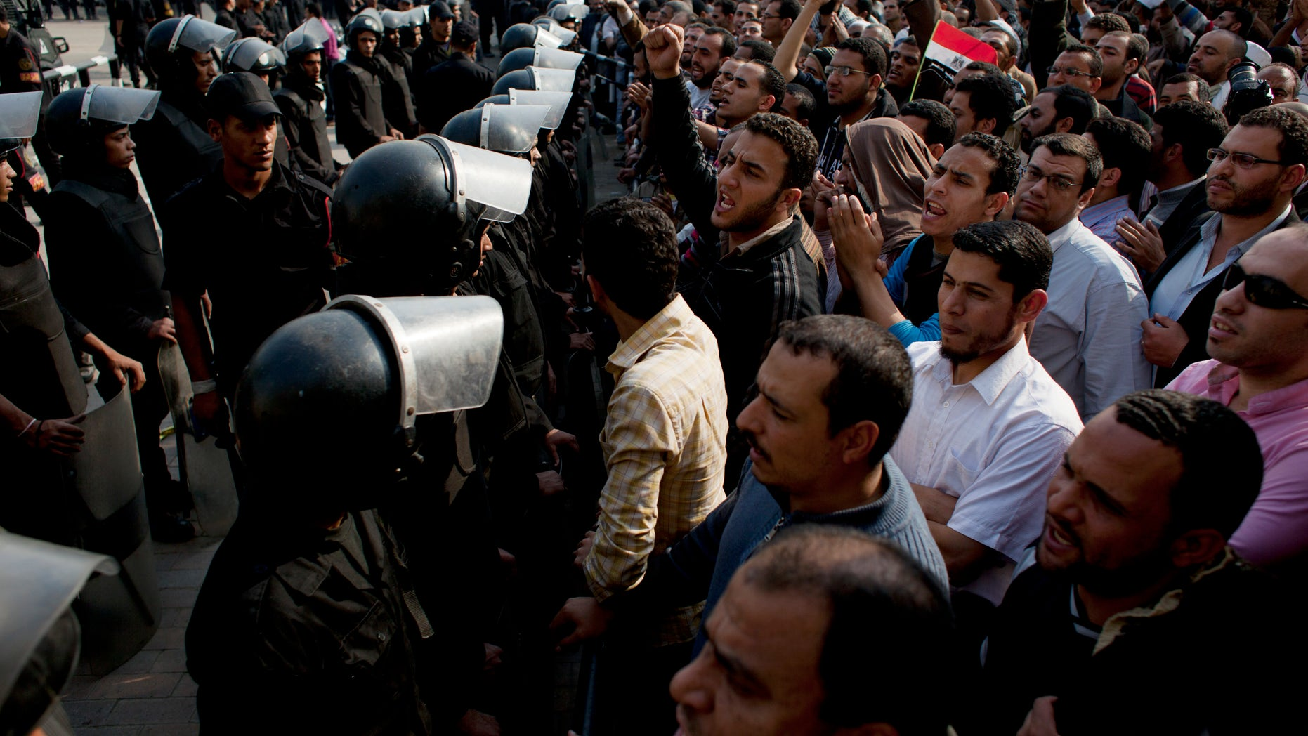 Dec. 2, 2012 - Supporters of Egyptian President Mohammed Morsi chant slogans as riot police stand guard in front of the entrance of Egypt's top court, in Cairo.