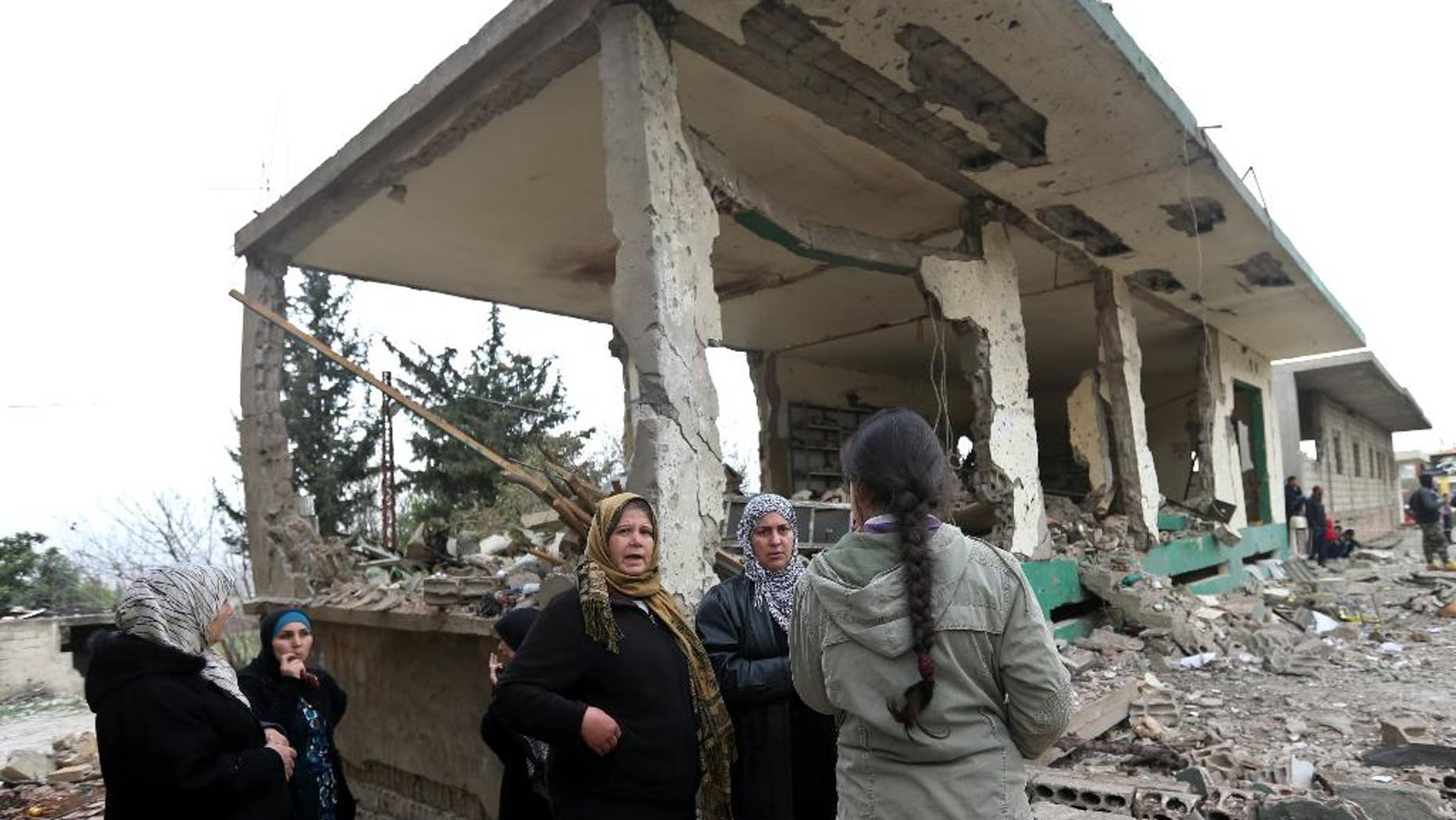 Lebanese women gather in front of damaged shops at the site of a deadly car bombing Sunday night, in the town of Nabi Othman, about 30 kilometers (18 miles) north of Baalbek, northeast Lebanon, Monday March 17, 2014. Lebanese security officials said the explosion killed at least two people and caused panic and massive destruction in the Hezbollah stronghold, which has a sizable Christian population in addition to Shiites. The civil war in neighboring Syria already has ignited polarizing sectarian tensions between Lebanon's Sunnis and Shiites. (AP Photo/Hussein Malla)