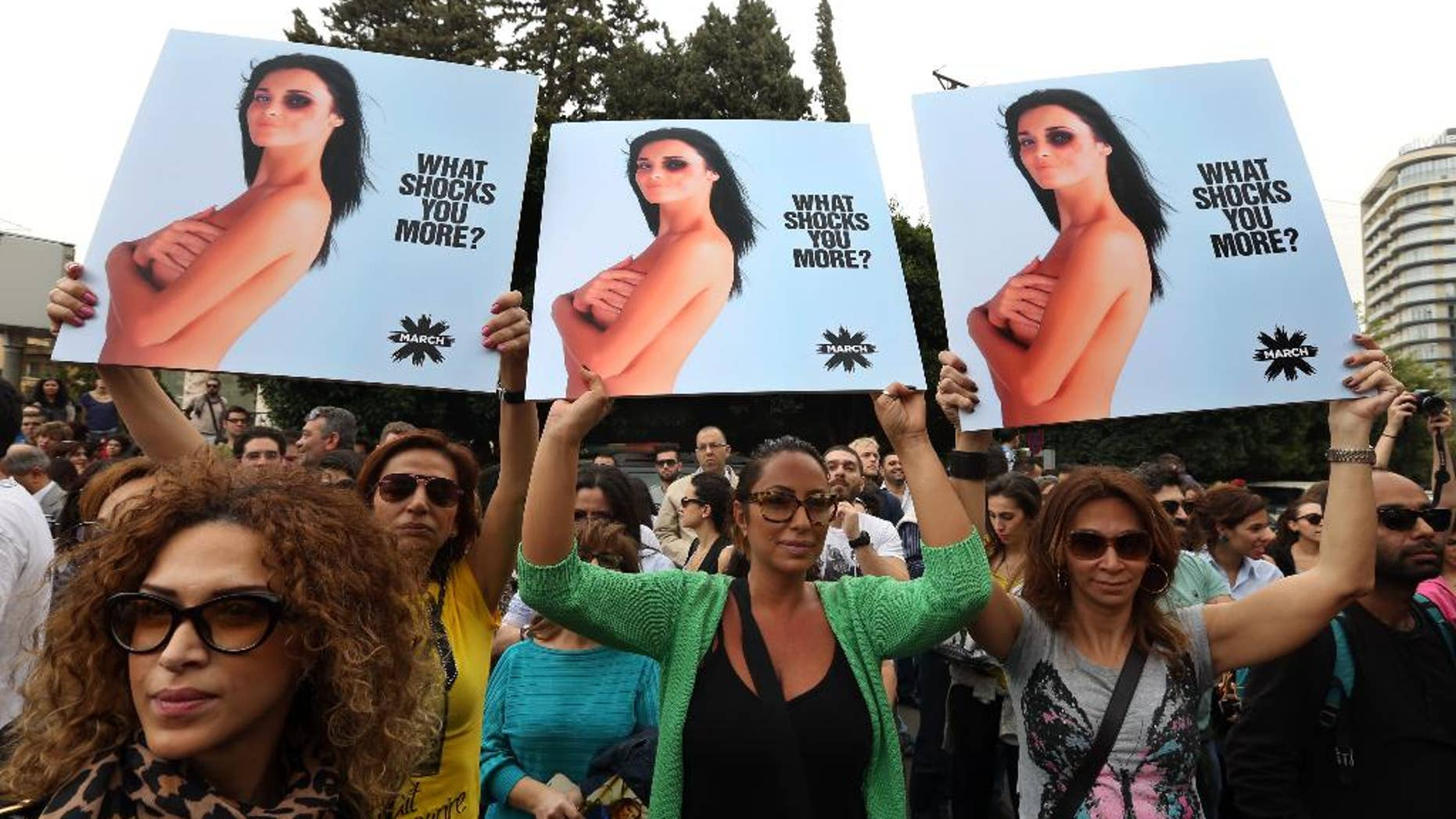 Lebanese women hold posters to mark International Woman's Day during a rally of thousands demanding that parliament approves a law that protects women from domestic violence, in Beirut, Lebanon, Saturday, March. 8, 2014. Although Lebanon appears very progressive on women rights compared to other countries in the Middle East, domestic violence remains an unspoken problem and the nation's parliament has yet to vote on a bill protecting women's rights nearly three years after it was approved by the Cabinet. (AP Photo/Bilal Hussein)