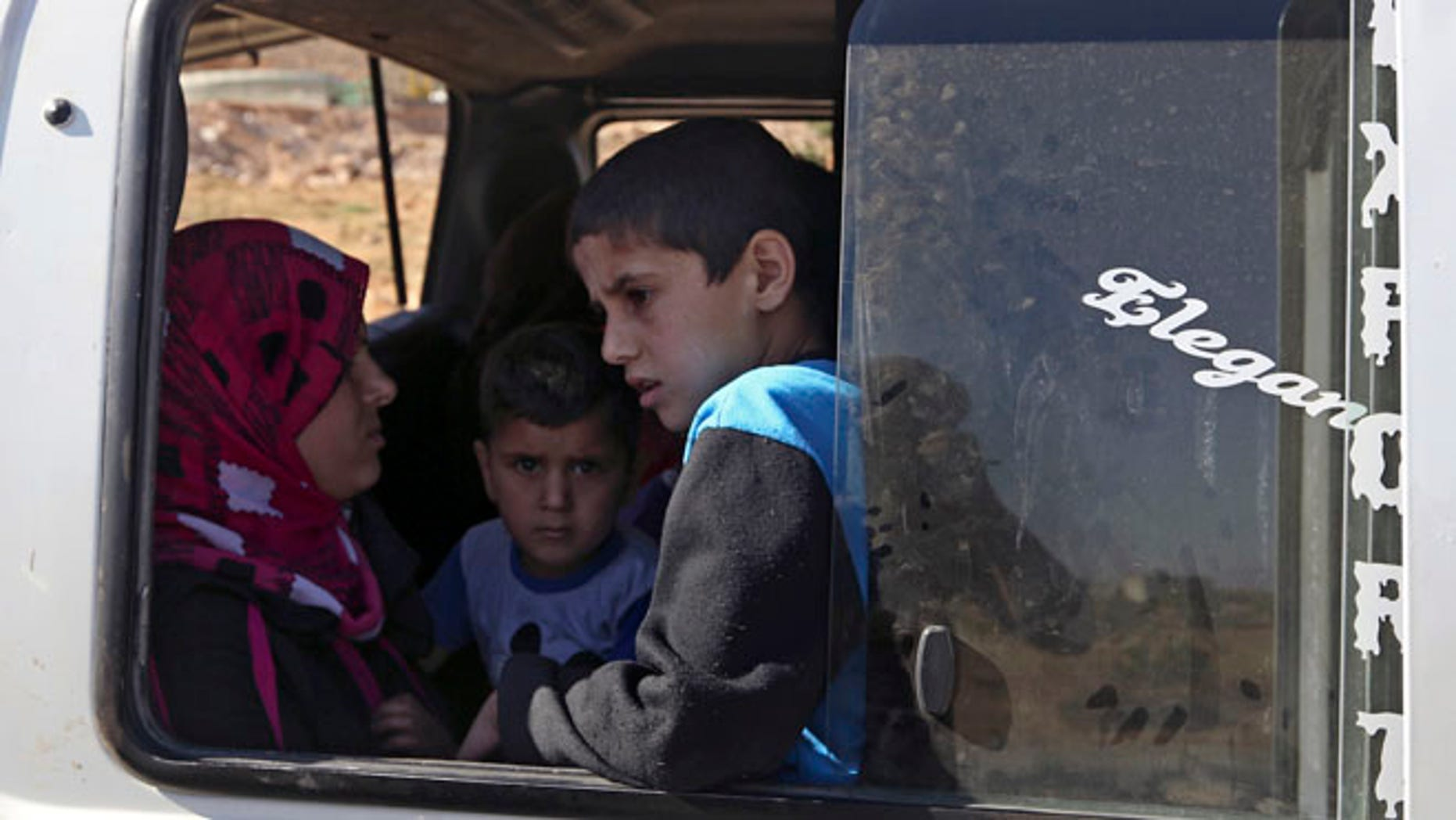 Aug. 4, 2014: A Lebanese family wait to depart in a minibus on the outskirts of Arsal, a predominantly Sunni Muslim town near the Syrian border in eastern Lebanon. (AP)
