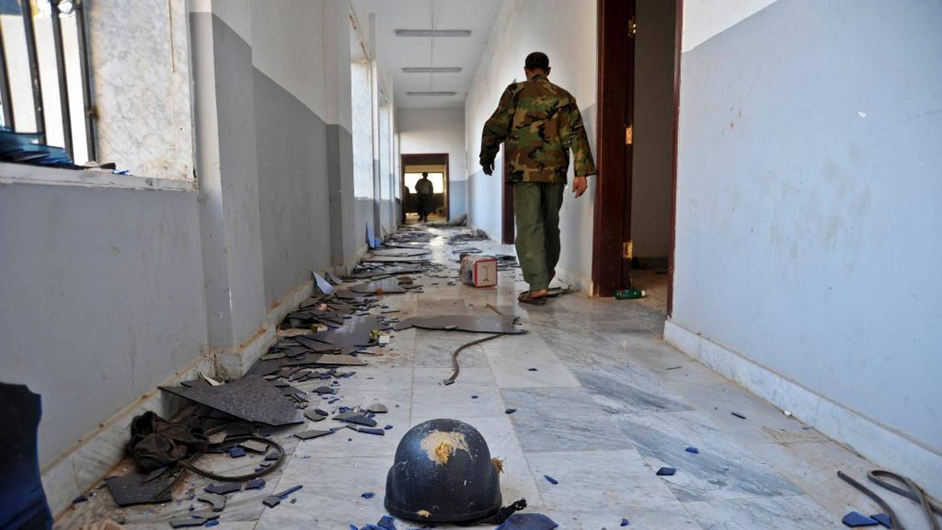 Nov. 3, 2014: In this photo, a Libyan military soldier walks past damages inside a building that was used by Islamic militias for fighting in Benghazi, Libya. (AP)