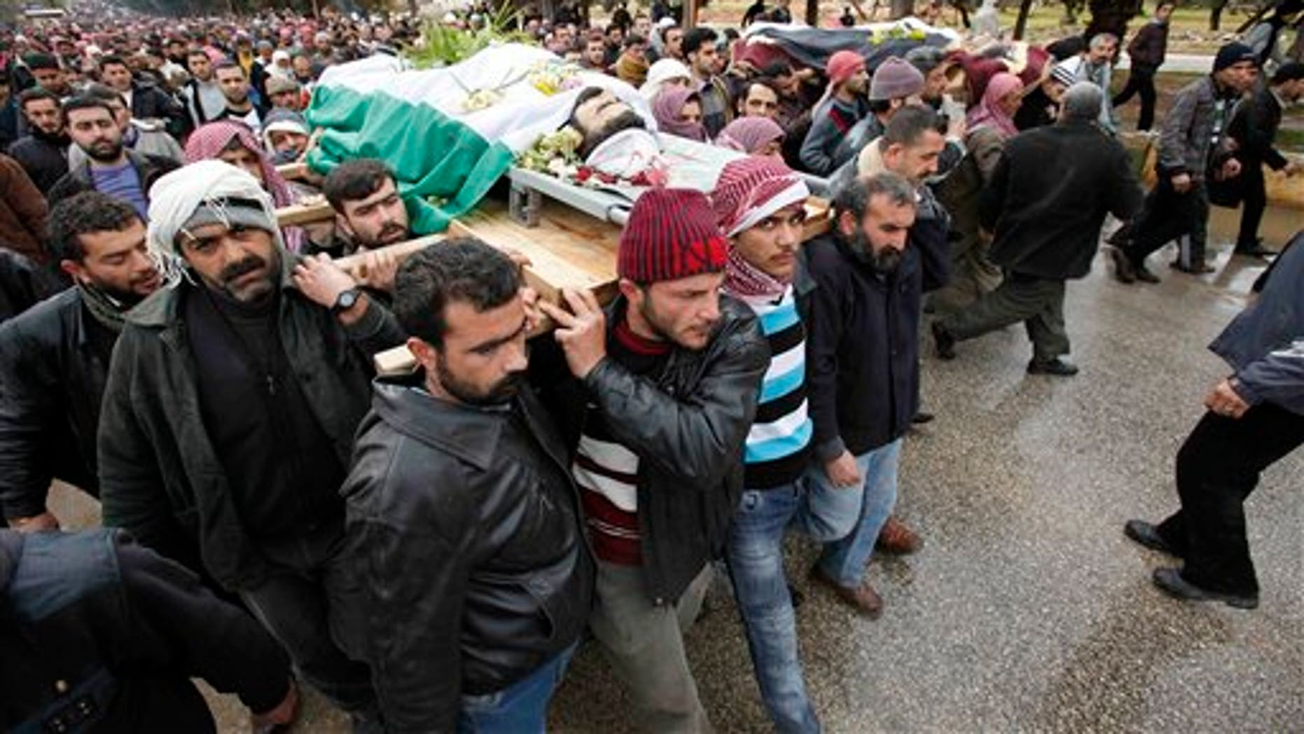 Feb. 9: Mourners carry a body during a funeral for a 10-year-old boy and rebel fighters killed during fighting in Idlib, Syria.