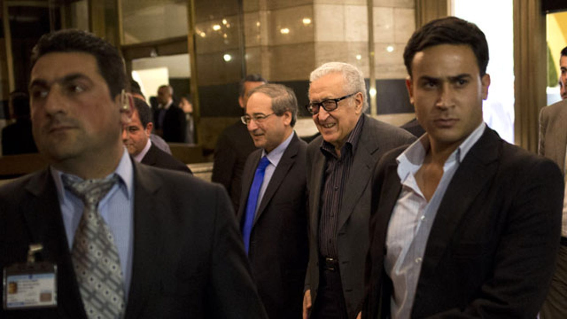 October 28, 2013: U.N.-Arab League envoy Lakhdar Brahimi, center right, and Deputy Syrian Foreign Minister Faisal Mekdad arrive to a hotel surrounded by security in Damascus, Syria. Brahimi is on his first trip to the country in almost a year. (AP Photo/Dusan Vranic)