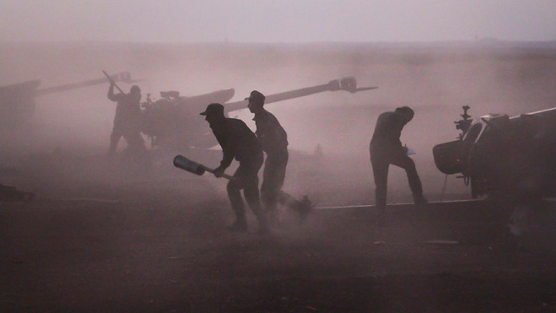 Oct. 7, 2015: Syrian army personnel load howitzers near the village of Morek in Syria.