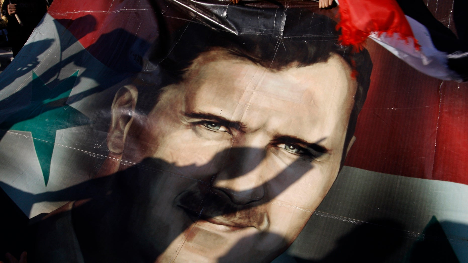 Dec. 16, 2011: Shadows of Syrians are reflected on a giant poster showing President Bashar Assad, during a supporting rally in Damascus, Syria.