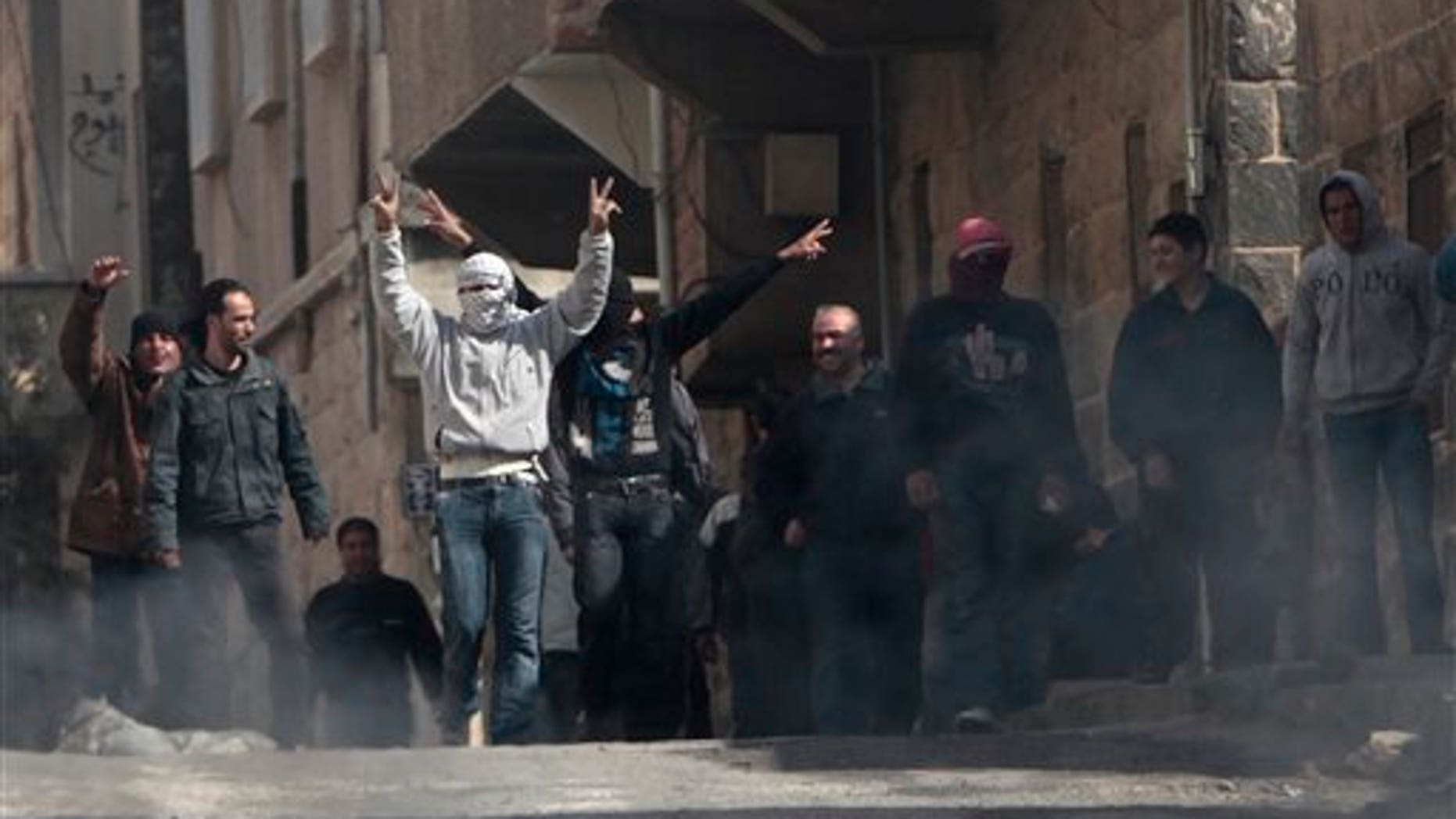 March 23: Anti-Syrian government protesters flash V sign as they protest in the southern city of Daraa, Syria. Syrian security forces shot live ammunition and tear gas near a mosque where protesters have been camped out in southern Syria, killing six people including a paramedic, activists said. The early morning attack near the al-Omari mosque in the southern city of Daraa marks the deadliest single day since anti-government protests inspired by uprisings across the Arab world reached this country last week. (AP)