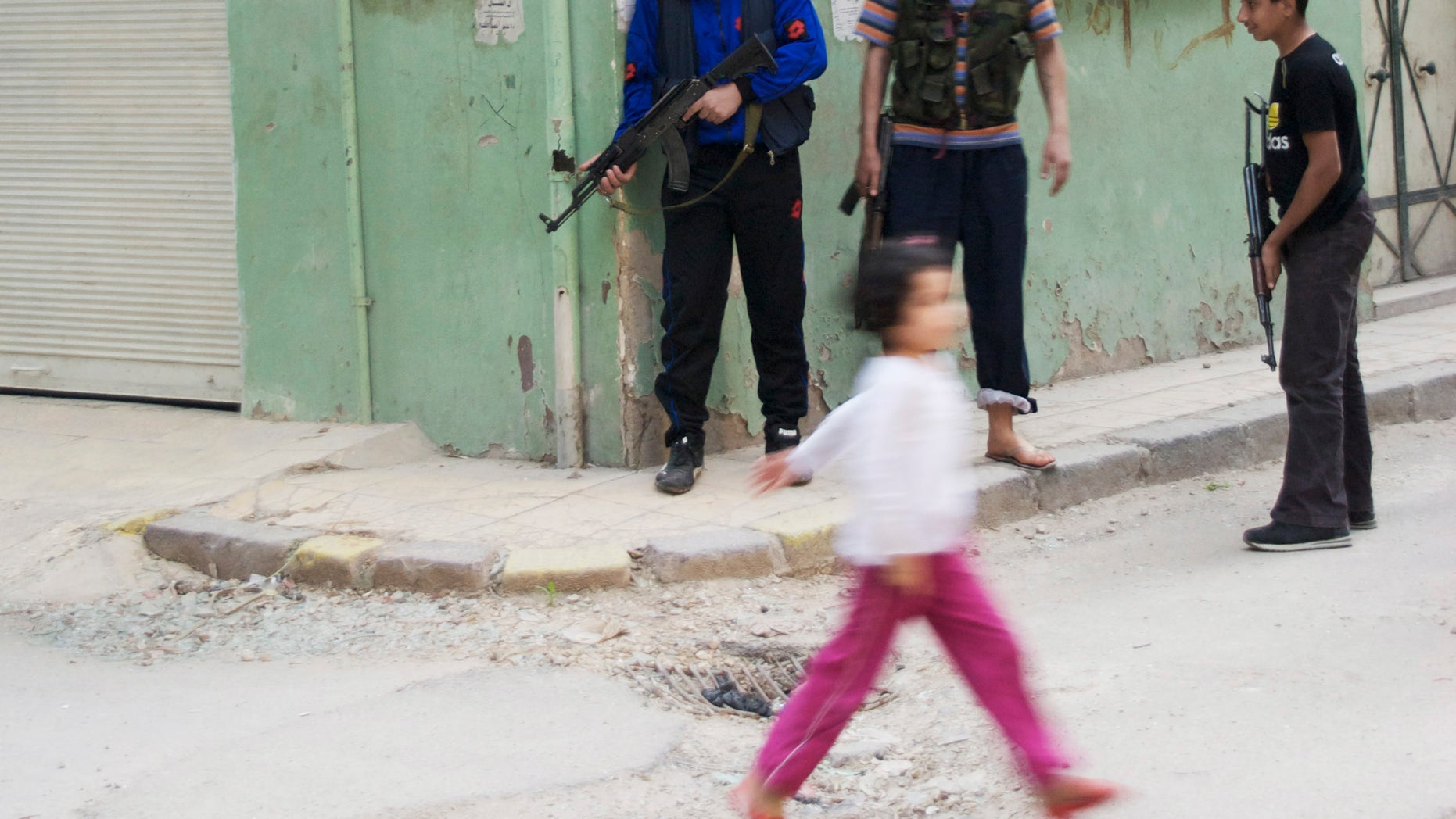 May 14, 2012: In this photo, a girl walks past Syrian rebels at Khaldiyeh neighborhood in Homs province, central Syria.