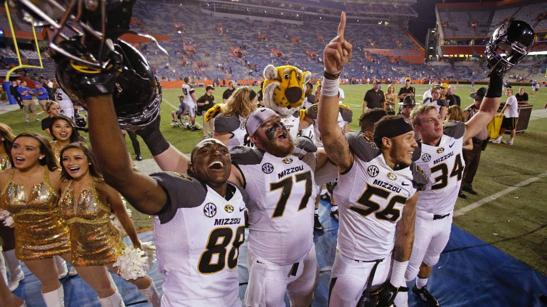 Missouri's Jimmie Hunt (88), Evan Boehm (77), Shane Ray (56) and Joey Burkett (34) celebrate in front of fans after Missouri defeated Florida 42-13 in an NCAA college football game in Gainesville, Fla., Saturday, Oct. 18, 2014. (AP Photo/John Raoux)