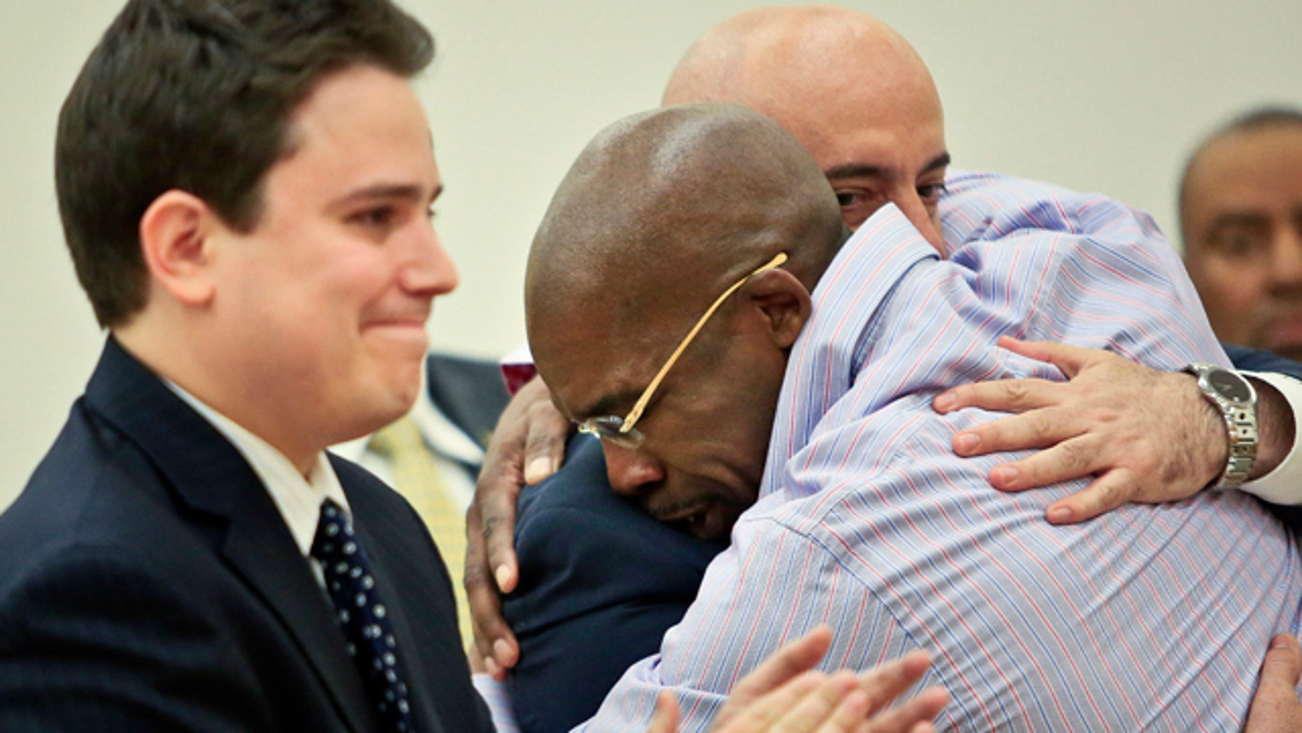 April 8, 2014: Jonathan Fleming, hugs his attorney Anthony Mayol while his other attorney Taylor Koss applaud in Brooklyn's Supreme Court, after a judge declared him a free man.  Fleming, who spent almost a quarter-century behind bars for murder, was cleared of a killing that happened when he was 1,100 miles away on a Disney World vacation in 1989. (AP Photo/Bebeto Matthews)