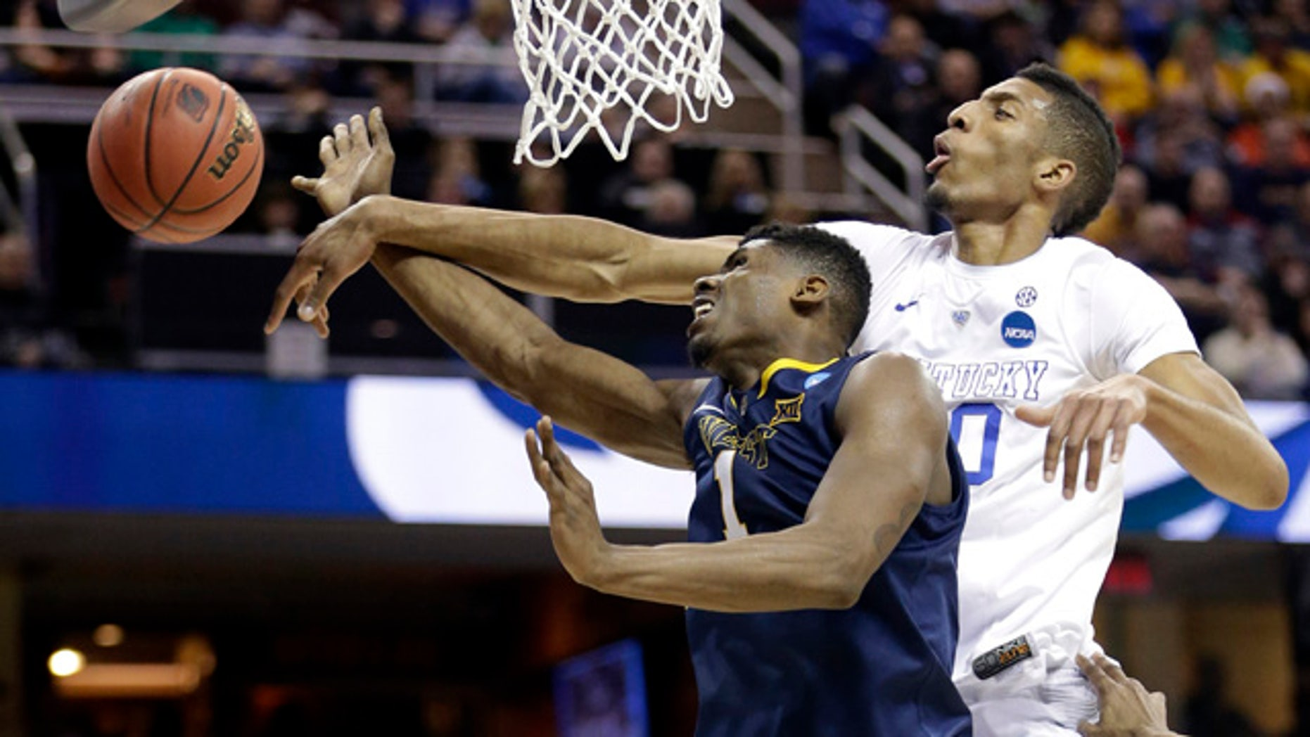 March 26, 2015: Kentucky's Marcus Lee, right, blocks a shot by West Virginia's Jonathan Holton during the first half of a college basketball game in the NCAA men's tournament regional semifinals in Cleveland. (AP Photo/Tony Dejak)