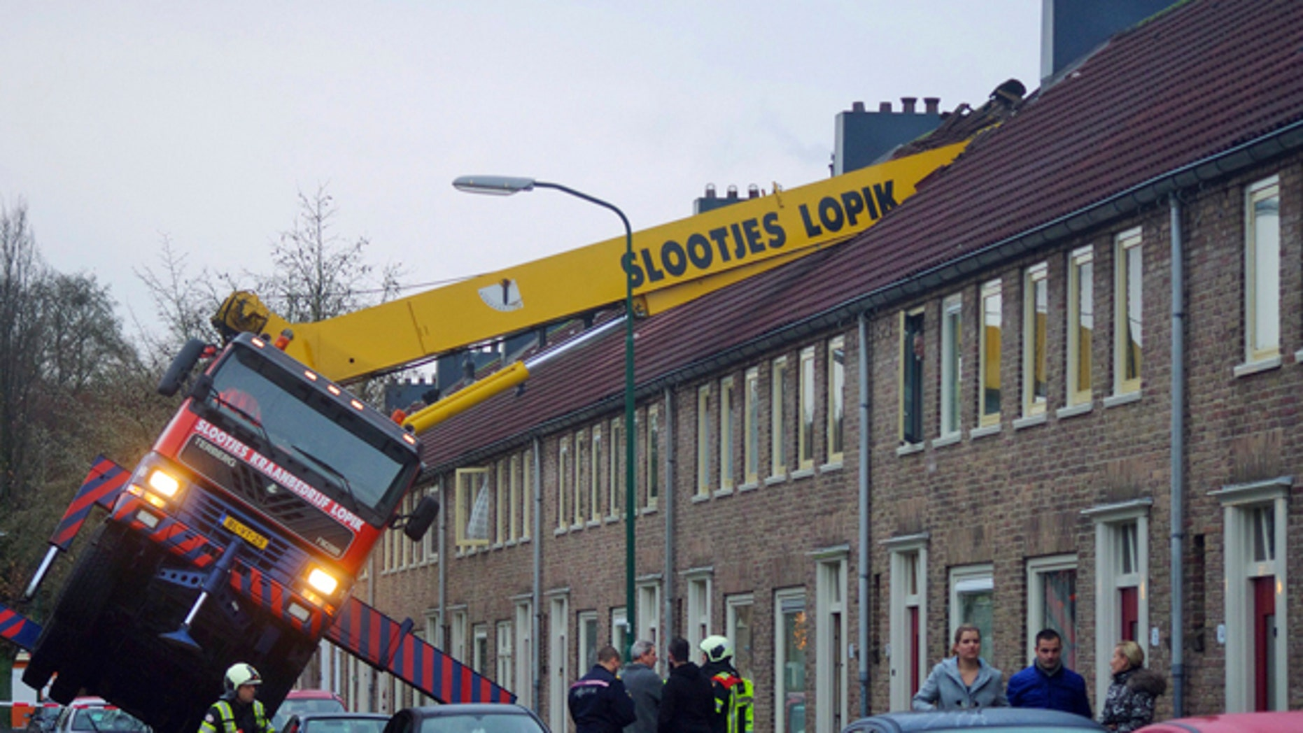 December 13, 2014: A crane which crashed into the roof of a house is seen following an unusual marriage proposal by a man who wished to be lifted in front of the bedroom window of his girlfriend to ask for her hand in marriage, in the Dutch town of IJsselstein. (AP/AS Media)