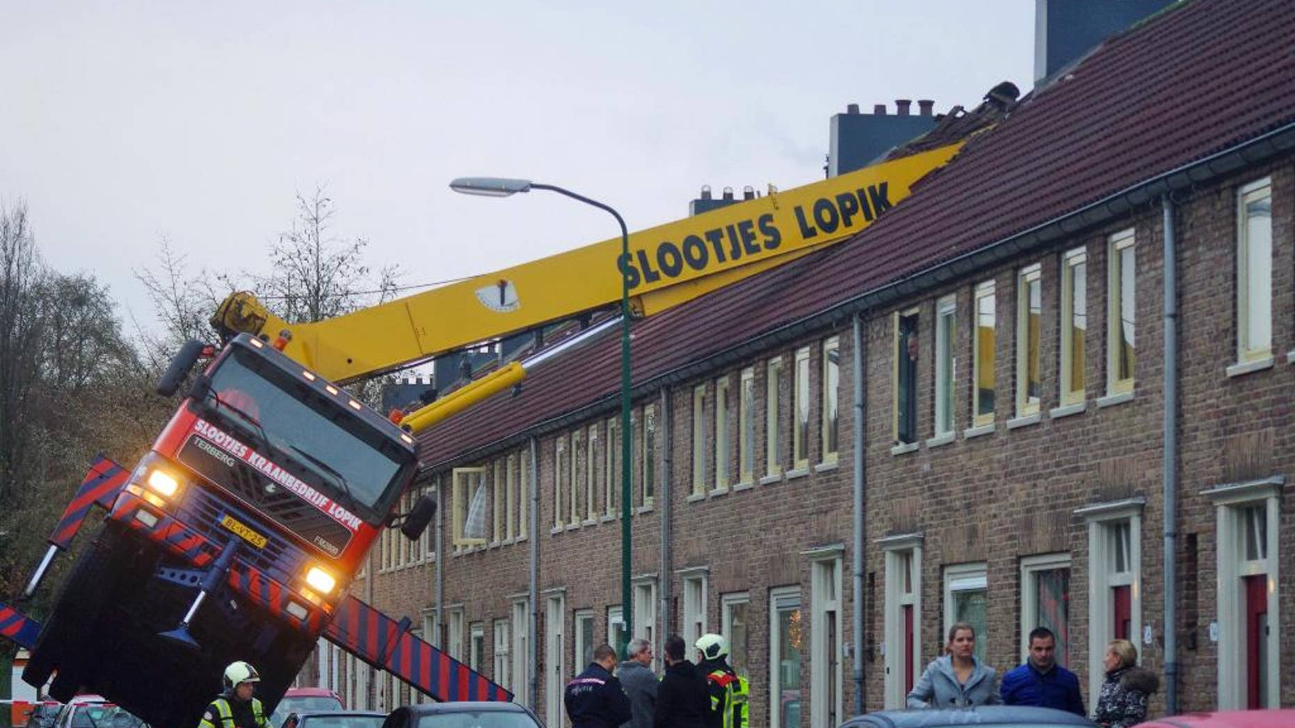 A crane which crashed into the roof of a house is seen following an unusual marriage proposal by a man who wished to be lifted in front of the bedroom window of his girlfriend to ask for her hand in marriage, in the central Dutch town of IJsselstein, Saturday Dec. 13, 2014. No people were injured in the accident, the groom-to-be jumped to safety without injuries and his girlfriend accepted to marry him, according to local Dutch media. (AP Photo/AS Media) NETHERLANDS OUT, MANDATORY CREDIT