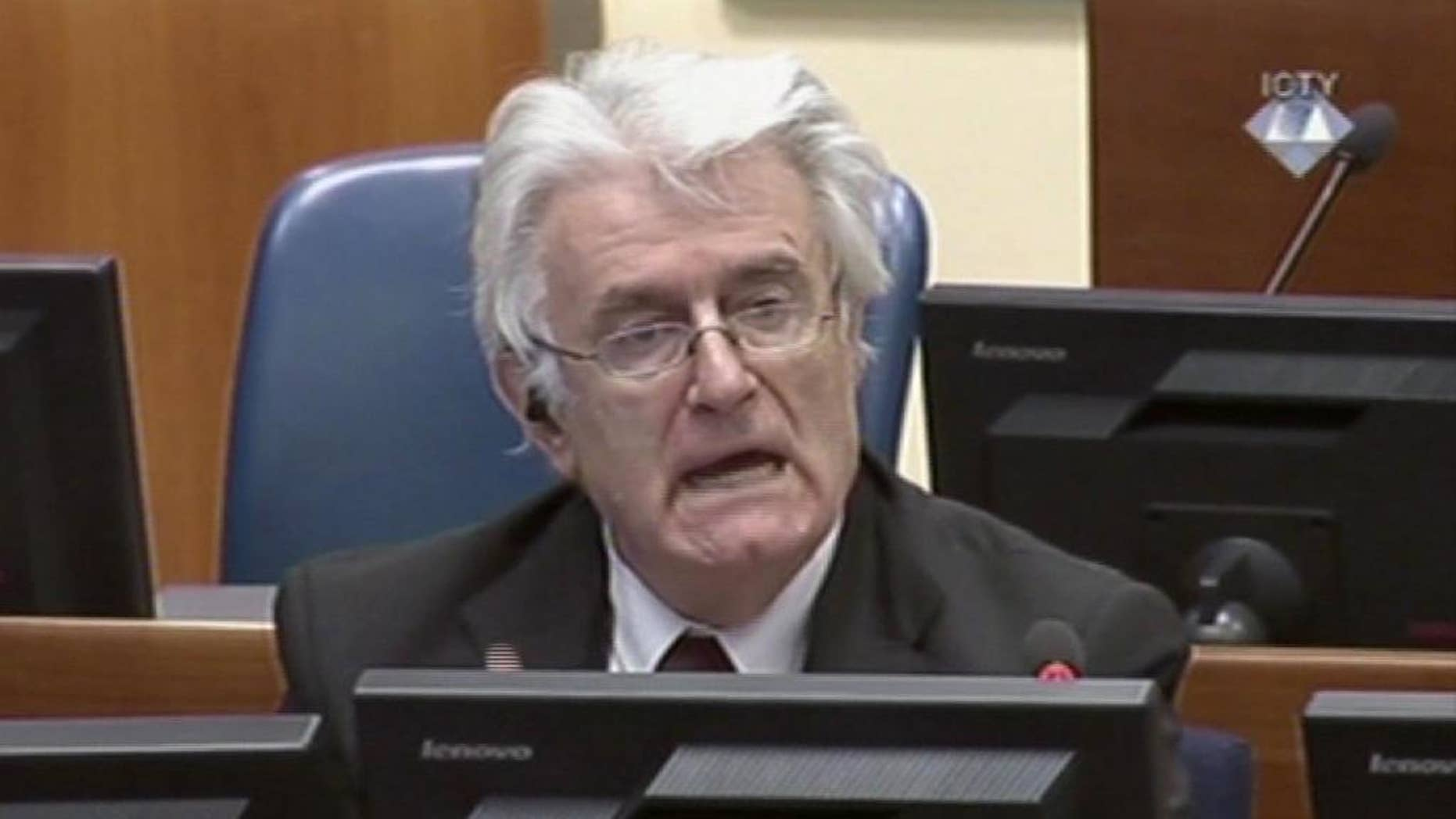 """Former Bosnian Serb leader Radovan Karadzic addresses the court of the International Criminal Tribunal for the former Yugoslavia in The Hague Netherlands in this image taken from TV, Wednesday Oct. 1, 2014. Karadzic insisted Wednesday that United Nations prosecutors do not have """"a shred of evidence"""" linking him to atrocities throughout the Bosnian war, and accused them of putting the entire Serb people on trial. In an 874-page written brief summarizing his defense, Karadzic said he should not be convicted by the U.N.'s Yugoslav war crimes tribunal, but acknowledged that, as wartime leader of the breakaway Serb entity in Bosnia, he """"bears moral responsibility for any crimes committed by citizens and forces of Republika Srpska."""" (AP Photo/ICTY via Associated Press Television)"""