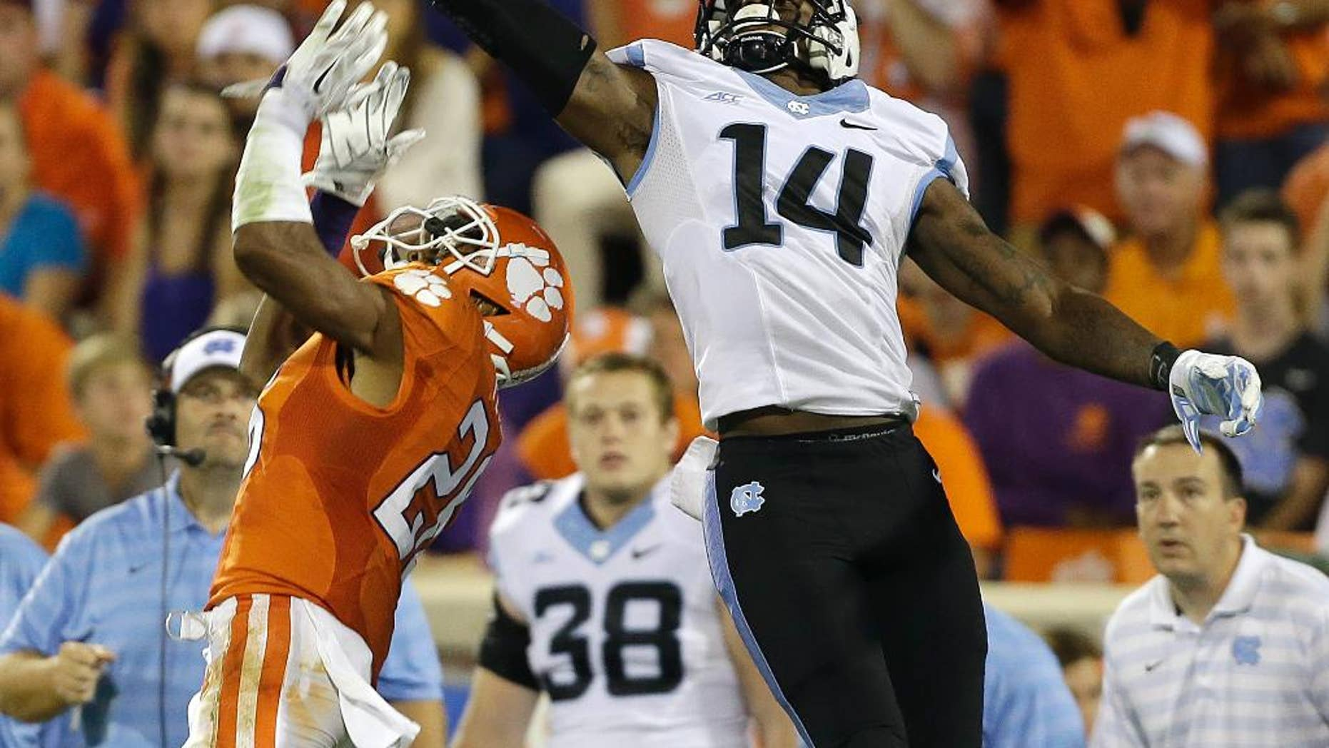 North Carolina's Quinshad Davis (14) stretches to make the catch as Clemson's Garry Peters (26) tries to break up the play during the second half of an NCAA college football game in Clemson, S.C., Saturday Sept. 27, 2014. Clemson won 50-35. (AP Photo/Bob Leverone)