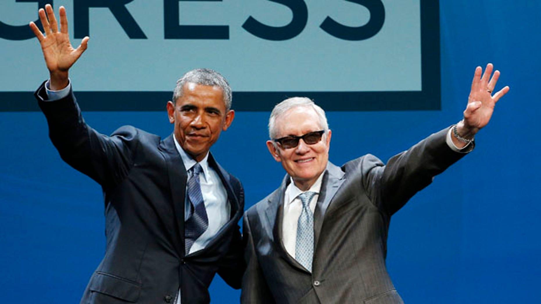 Aug. 24, 2015: President Barack Obama, left, and Senate Minority Leader Sen. Harry Reid wave onstage at the National Clean Energy Summit in Las Vegas. (AP Photo/John Locher)