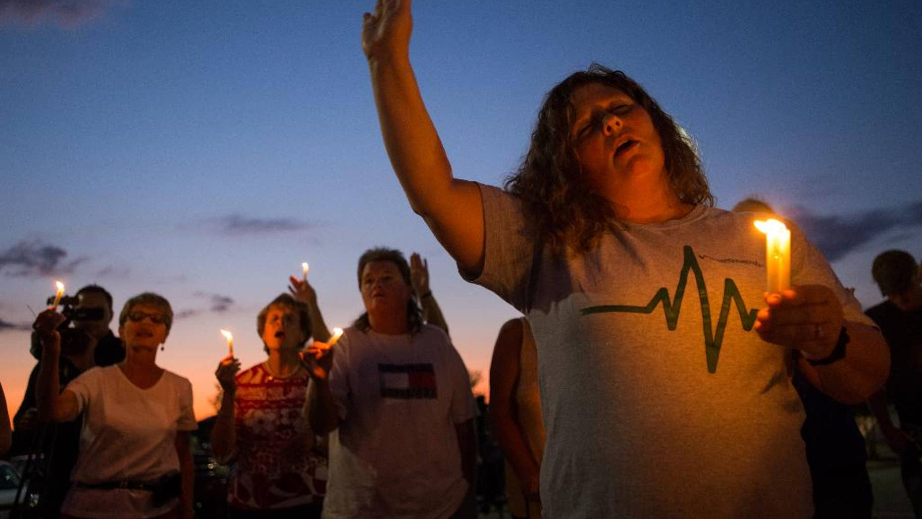 Stephanie Gray attends a vigil for journalists Alison Parker and Adam Ward who were killed during a shooting at Bridgewater Plaza in Moneta, Va., Wednesday, Aug. 26, 2015. Vester Lee Flanagan opened fire during a live on-air interview for WDBJ, killing the two journalists Wednesday. (Autumn Parry/The News & Advance via AP)