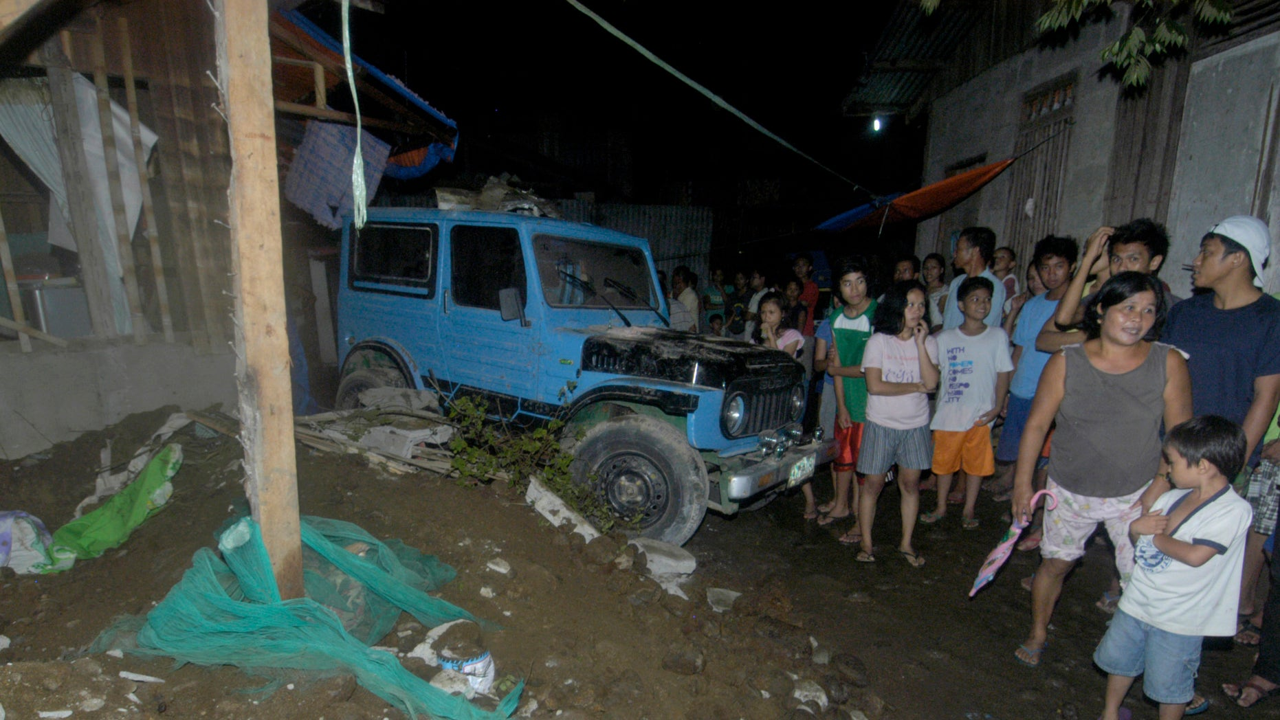 Residents gather at a collapsed house in Cagayan De Oro city, southern Philippines following a 7.6-magnitude earthquake that struck off the Philippines eastern coast late Friday Aug.31, 2012. The quake set off car alarms, shook items off shelves and sent many coastal residents fleeing for high ground before authorities lifted all tsunami warnings they had issued for the Philippines and neighboring countries from Indonesia to Japan, and for Pacific islands as far away as the Northern Marianas. (AP Photo/Froilan Gallardo)