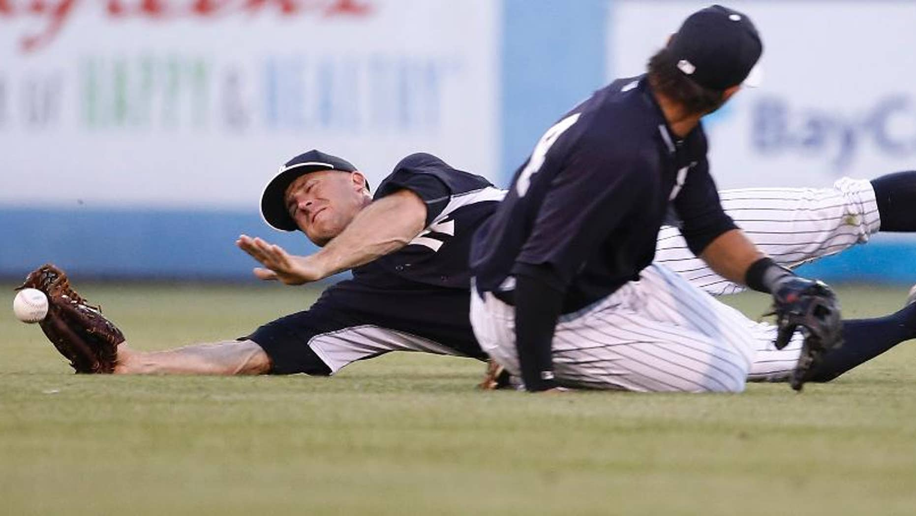 New York Yankees center fielder Brett Gardner loses the ball trying to catch a fly ball hit by Pittsburgh Pirates' Jordy Mercer while nearly colliding with Yankees second baseman Brian Roberts during the second inning of a spring exhibition baseball game against the Pittsburgh Pirates in Tampa, Fla., Friday, March 21, 2014. Mercer advanced to second on the play. (AP Photo/Kathy Willens)