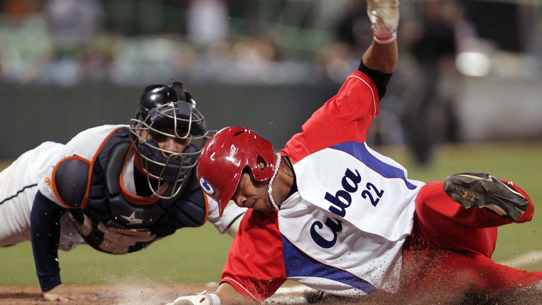 Cubaâs Yadiel Hernandez, right, slides safe at the home plate against Venezuela's catcher Jose Gil during a Caribbean Series baseball semifinal game in San Juan, Puerto Rico, Saturday, Feb. 7, 2015. (AP Photo/Ricardo Arduengo)
