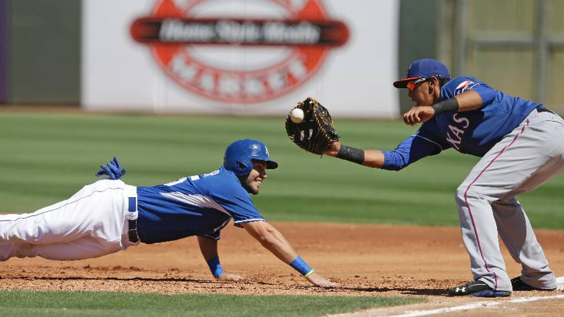 Kansas City Royals' Eric Hosmer is picked off at first base as Texas Rangers' Ronald Guzman applies the tag during the second inning of a spring exhibition baseball game, Saturday, March 22, 2014, in Surprise, Ariz. (AP Photo/Darron Cummings)