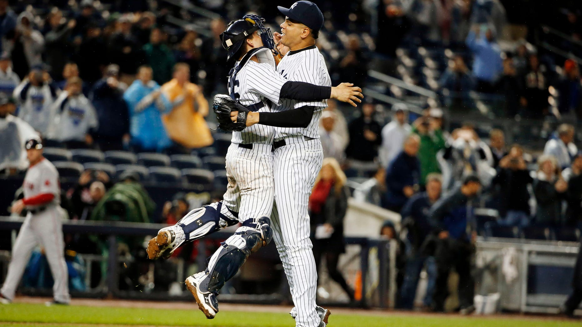 New York Yankees catcher John Ryan Murphy, left and New York Yankees pitcher Dellin Betances celebrate after the Yankees clinched a wild-car berth in the playoffs by defeating the Boston Red Sox 4-1 in a baseball game in New York, Thursday, Oct. 1, 2015. (AP Photo/Kathy Willens)