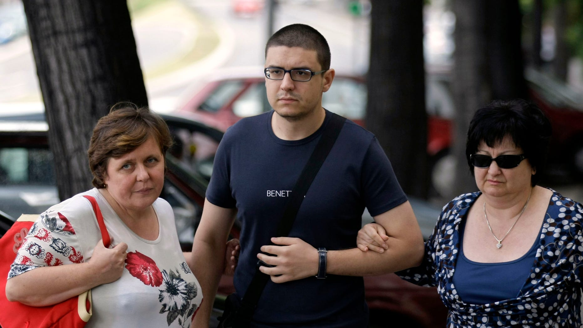 Goran Hadzic's son Srecko Hadzic, center, wife Zivka Hadzic, right and sister Goranka Meseldzija, arrive at the Special Court building in Belgrade, Serbia, Thursday, July 21, 2011.