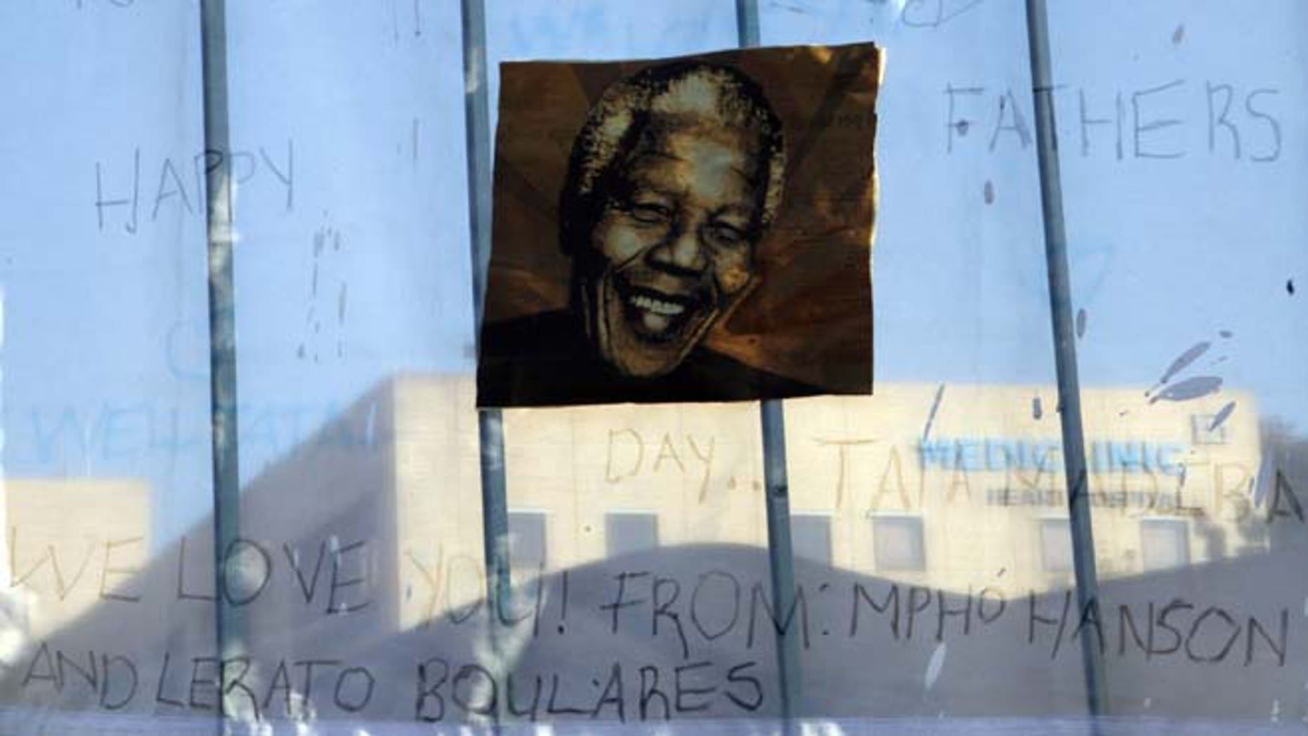 A print of Nelson Mandela and get-well messages hanged outside of the Mediclinic Heart Hospital where former South African President Nelson Mandela is being treated in Pretoria, South Africa Monday, June 24, 2013. Mandela's health has deteriorated and he is now in critical condition, the South African government said.