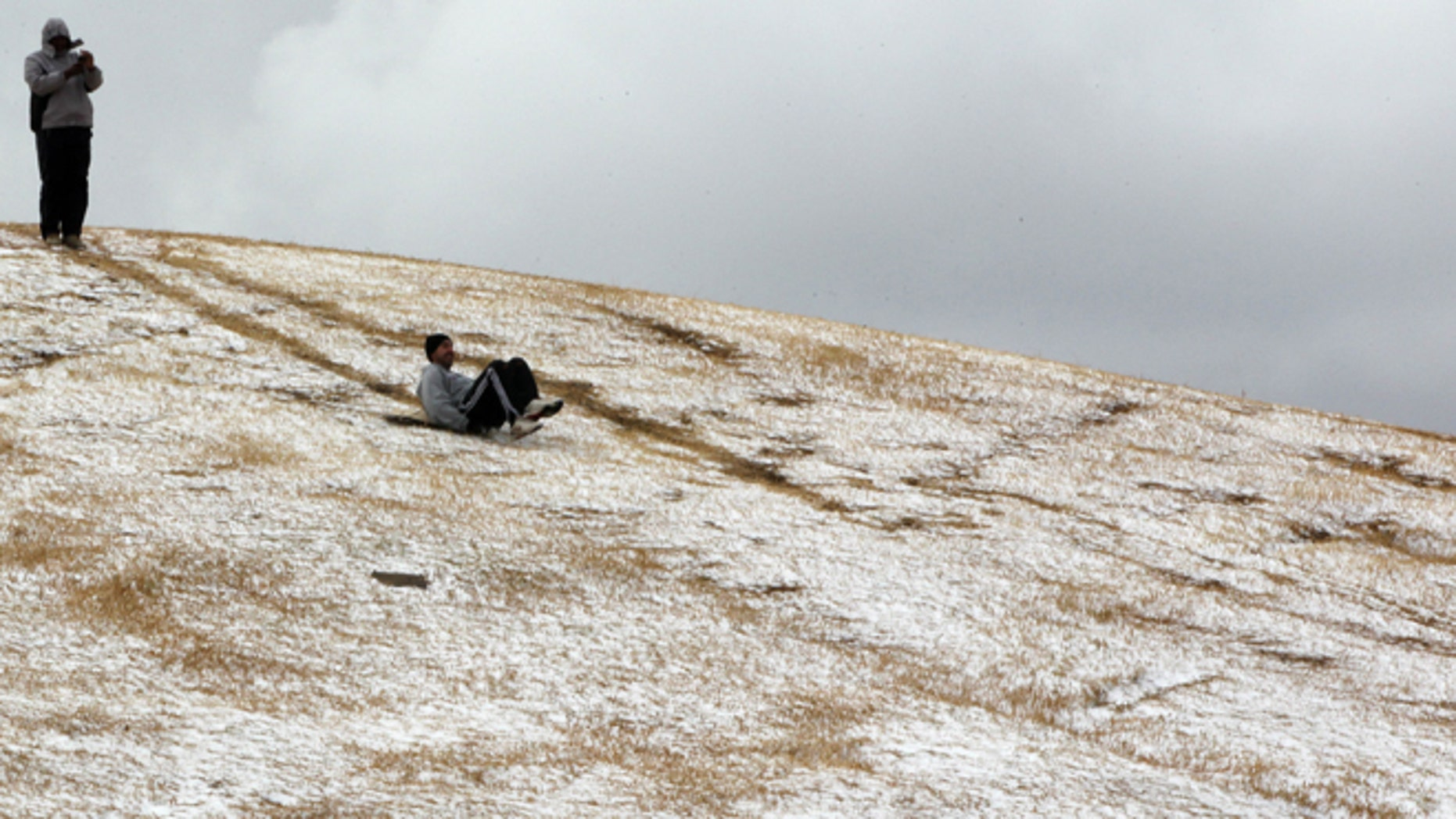 Aug. 7, 2012: A man slides down a hill after a rare snowfall in Johannesburg, South Africa.