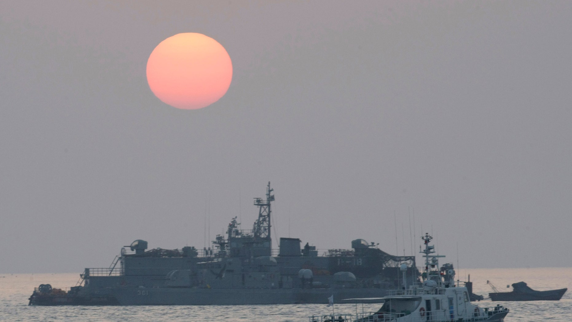 A government ship sails past the South Korean Navy's floating base as the sun rises near Yeonpyeong island, South Korea, Wednesday, Dec. 22, 2010.