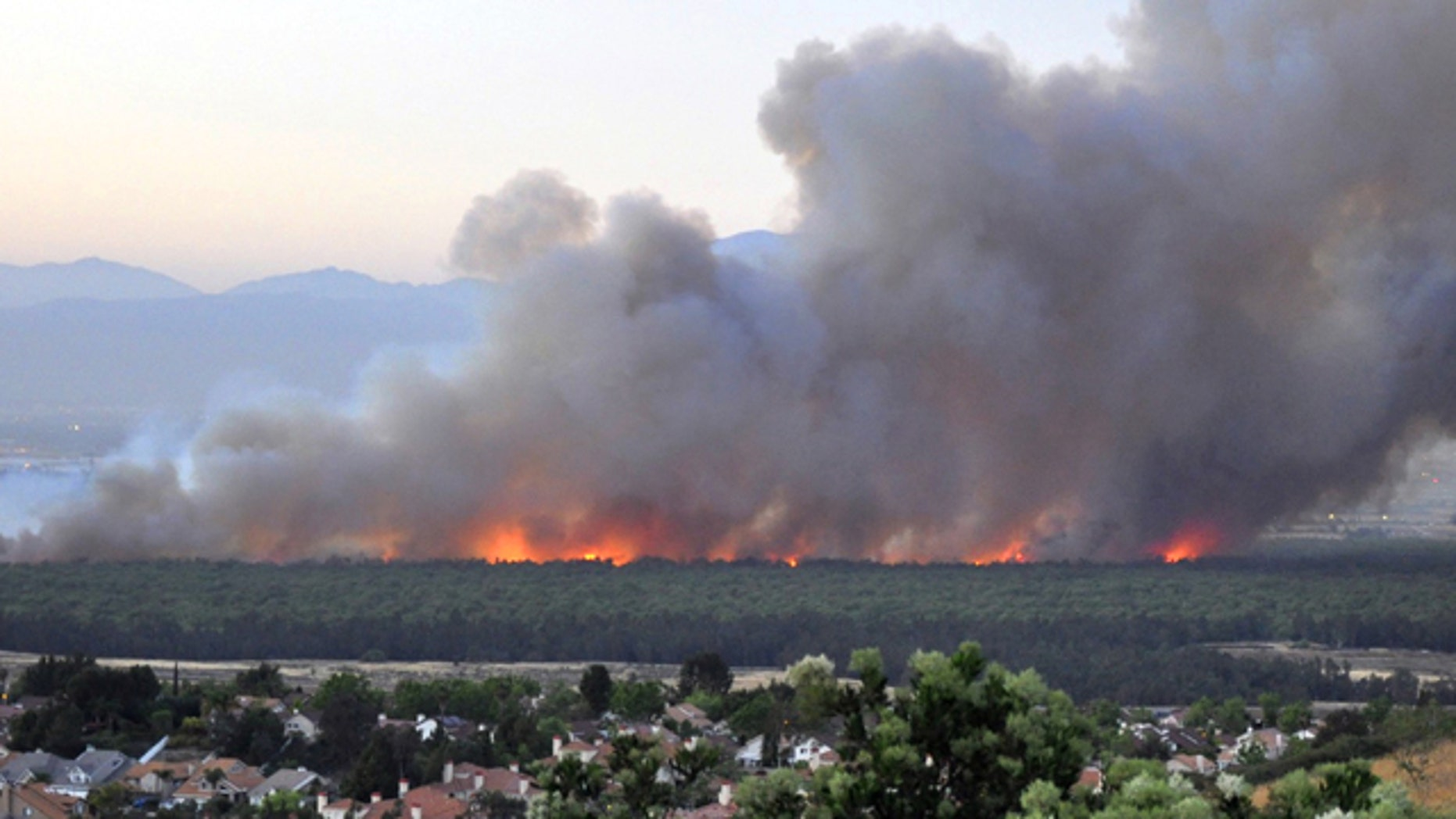 April 18, 2015: In this photo provided by Daniel Cole, flames burn in the Prado Dam Flood Control Basin adjacent to homes, foreground, as seen from Corona, Calif. (Daniel Cole via AP)