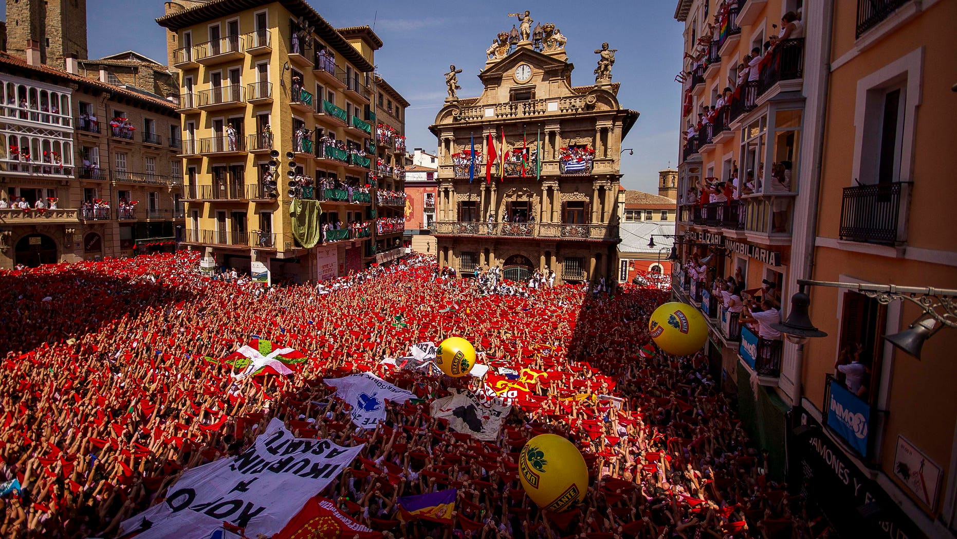 """Revelers hold up traditional red neckties during the launch of the """"Chupinazo"""" rocket, to celebrate the official opening of the 2015 San Fermin fiestas in Pamplona, Spain, Monday, July 6, 2015. Revelers from around the world turned out here to kick off the festival with a messy party in the Pamplona town square, one day before the first of eight days of the running of the bulls. (AP Photo/Andres Kudacki)"""