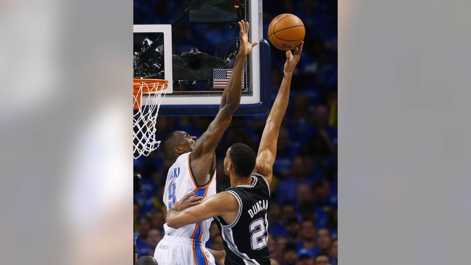 Oklahoma City Thunder forward Serge Ibaka (9) gets up to block a shot by San Antonio Spurs forward Tim Duncan (21) in the first quarter of Game 3 of an NBA basketball playoff series of the Western Conference finals, Sunday, May 25, 2014, in Oklahoma City. (AP Photo/Sue Ogrocki)