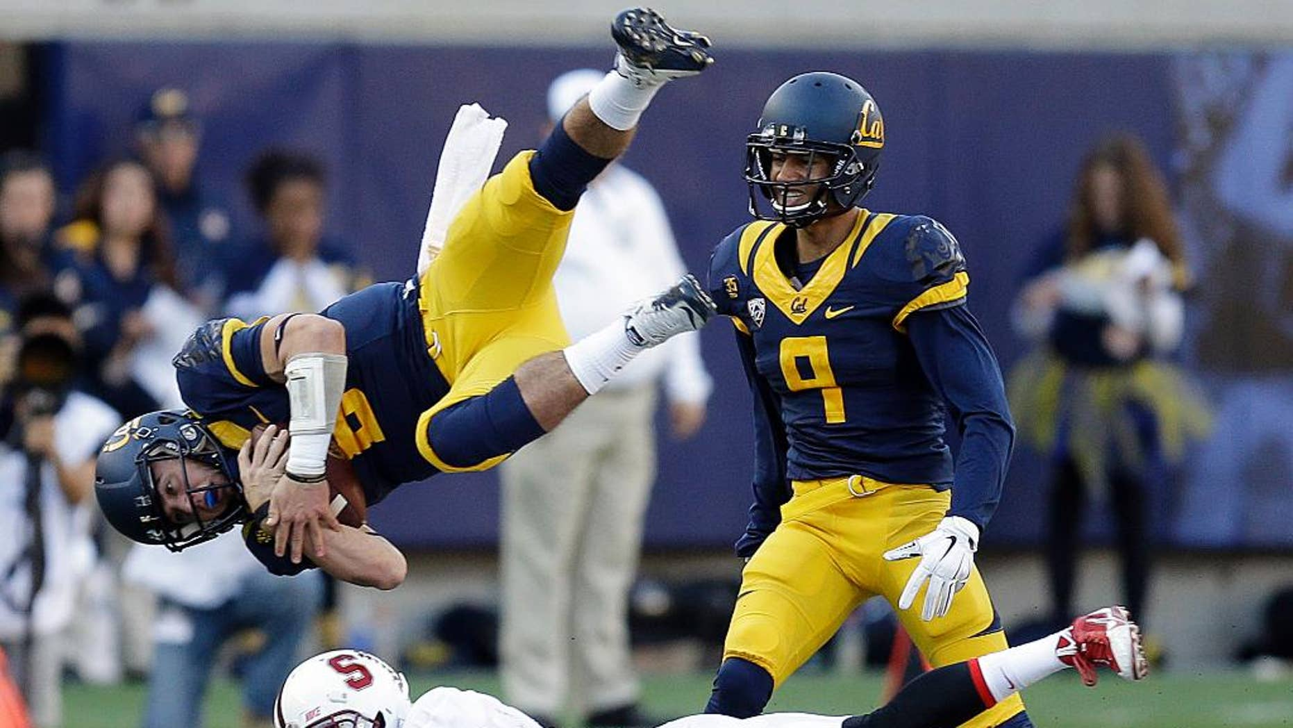 Stanford's Ronnie Harris (21) upends California quarterback Luke Rubenzer (8) during the second half of an NCAA college football game Saturday, Nov. 22, 2014, in Berkeley, Calif. At right is California's Trevor Davis (9). (AP Photo/Ben Margot)