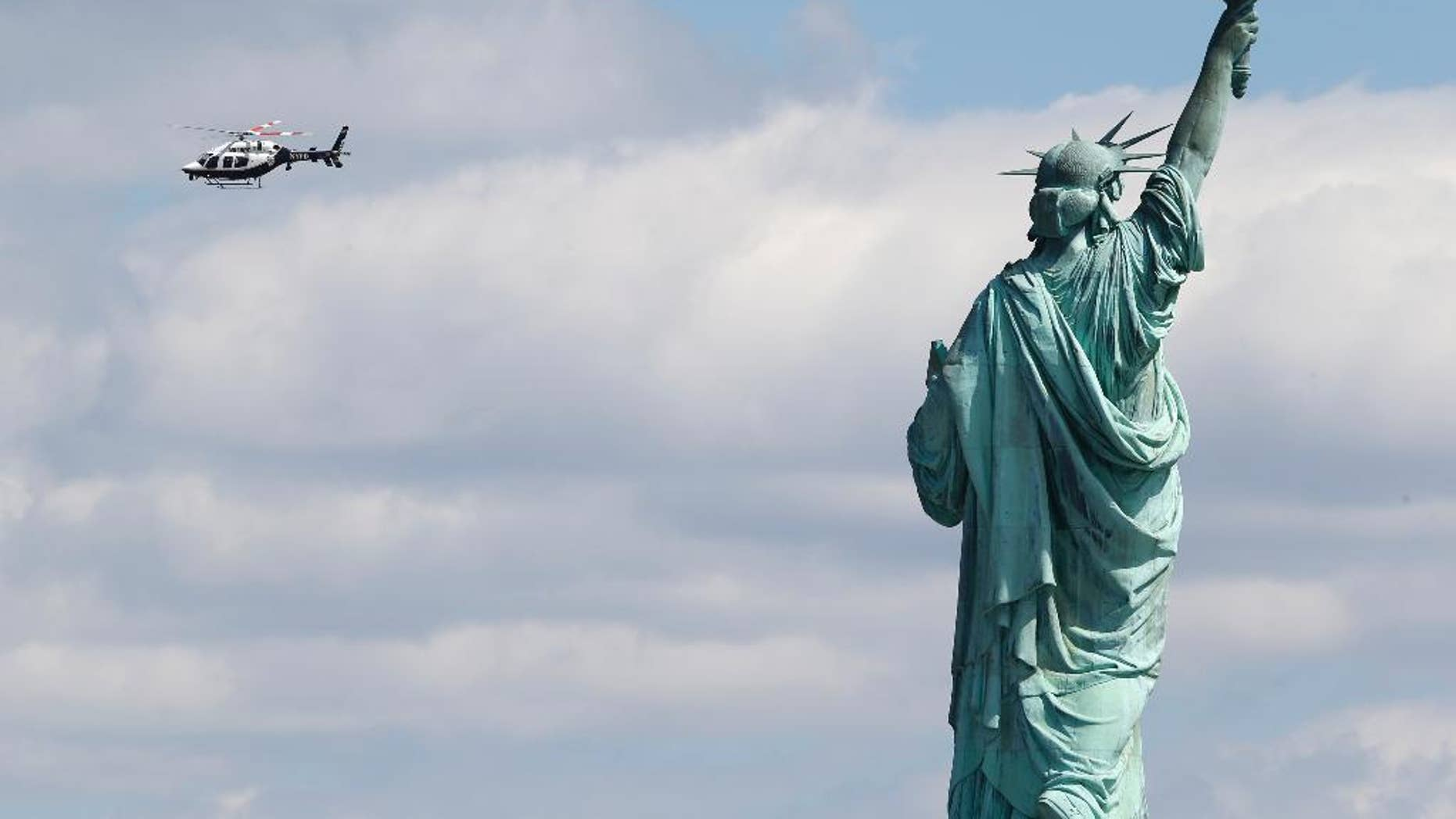 A New York Police helicopter circles over  Liberty Island where the Statue of Liberty was evacuated with officers responding to a report of a suspicious package seen from Jersey City, N.J., Friday, April 24, 2015. Visitors are posting photos online showing hundreds of people being herded toward a ferry landing. Tourists say they were taken off boats while trying to leave nearby Ellis Island. Those vessels then were used to evacuate Liberty Island. (AP Photo/Julio Cortez)