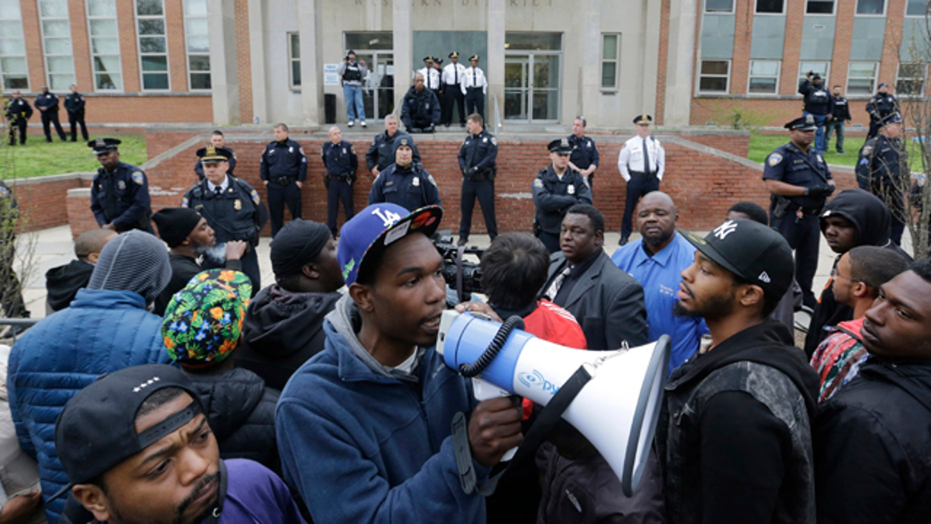 April 23, 2015: Protesters for Freddie Gray stand outside the Baltimore Police Department's Western District police station. Gray died from spinal injuries about a week after he was arrested and transported in a police van. (AP Photo/Patrick Semansky)