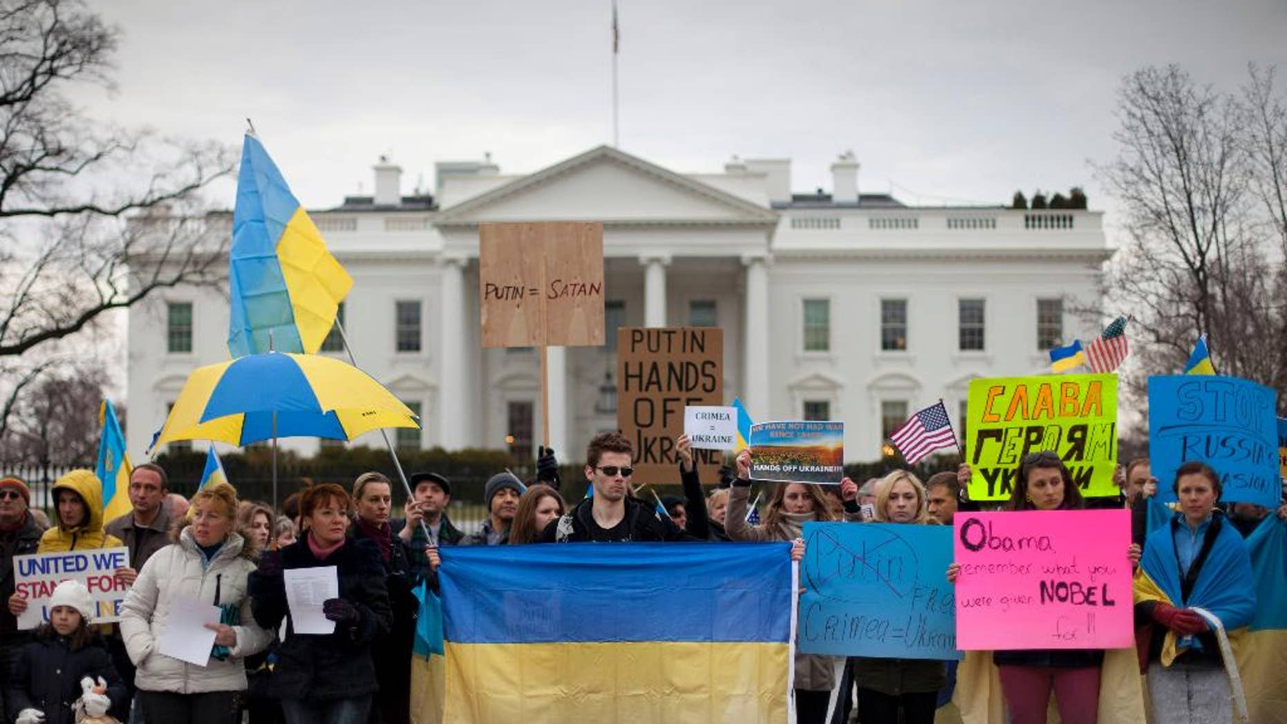 Demonstrators gather outside the White House in Washington, Saturday, March 1, 2014. Russian troops took over Crimea as the parliament in Moscow gave President Vladimir Putin a green light Saturday to use the military to protect Russian interests in Ukraine. (AP Photo/Pablo Martinez Monsivais)