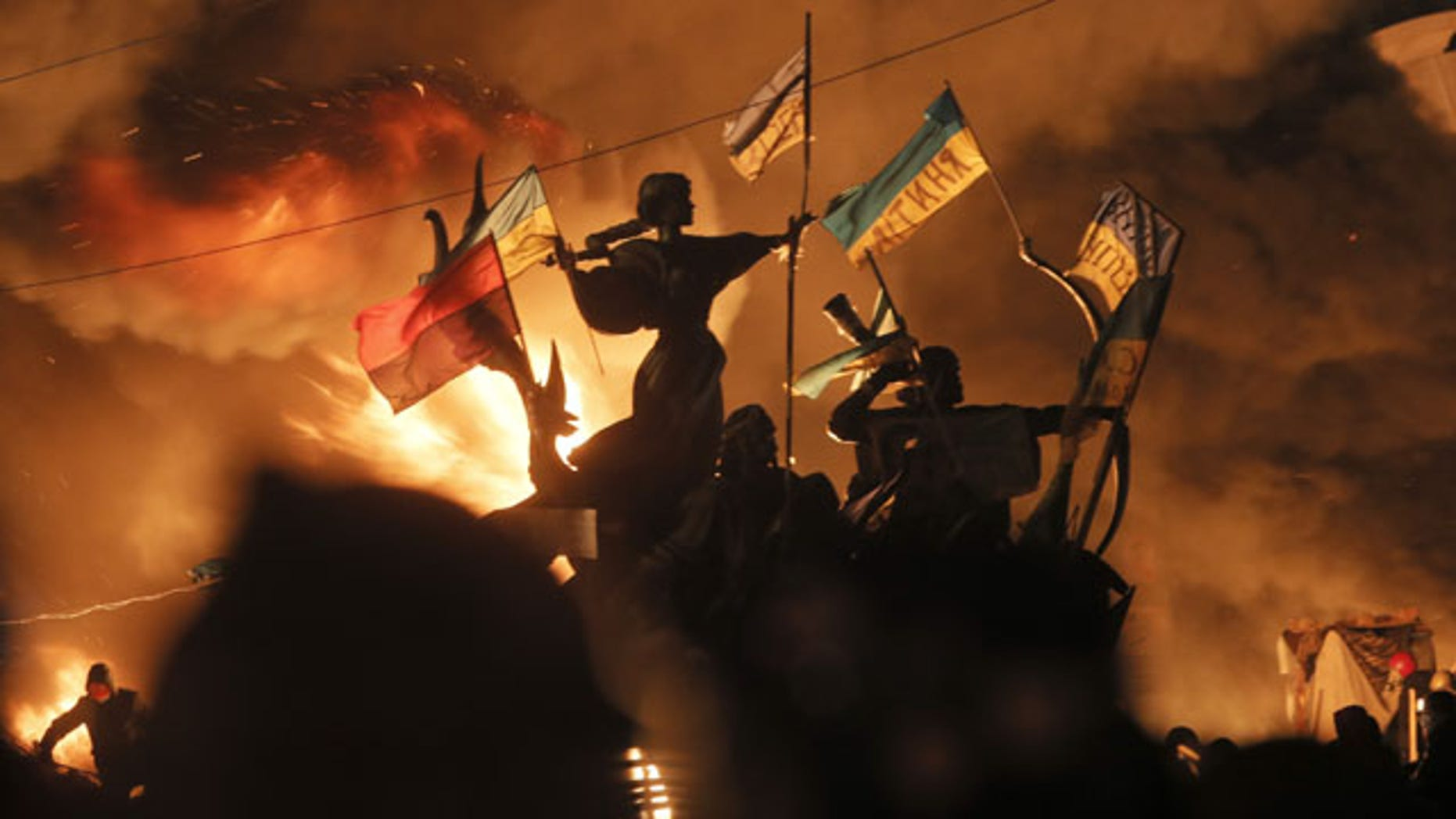 February 18, 2014: Monuments to Kiev's founders burn as anti-government protesters clash with riot police in Independence Square, the epicenter of Ukraine's current unrest. (AP)